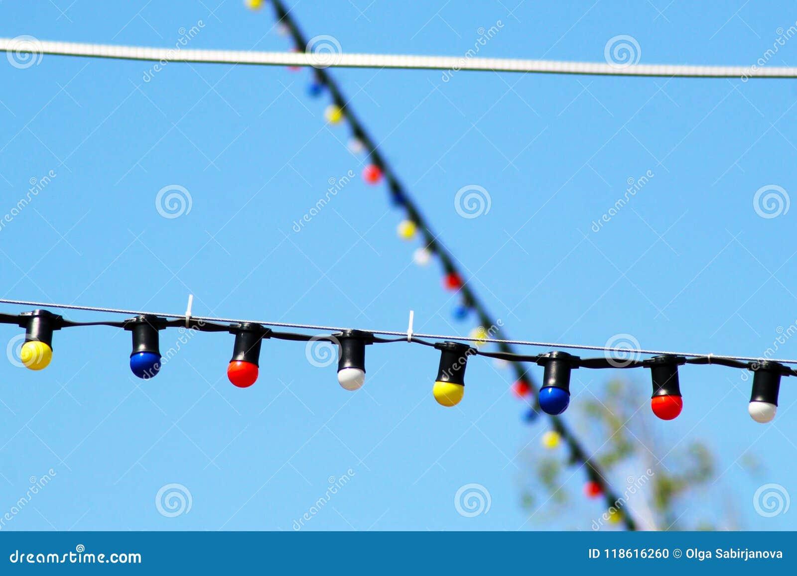 Jeden długa elektryczna girlanda dla zaświecać z światło białe żarówkami przeciw tłu błękitny jasny niebo