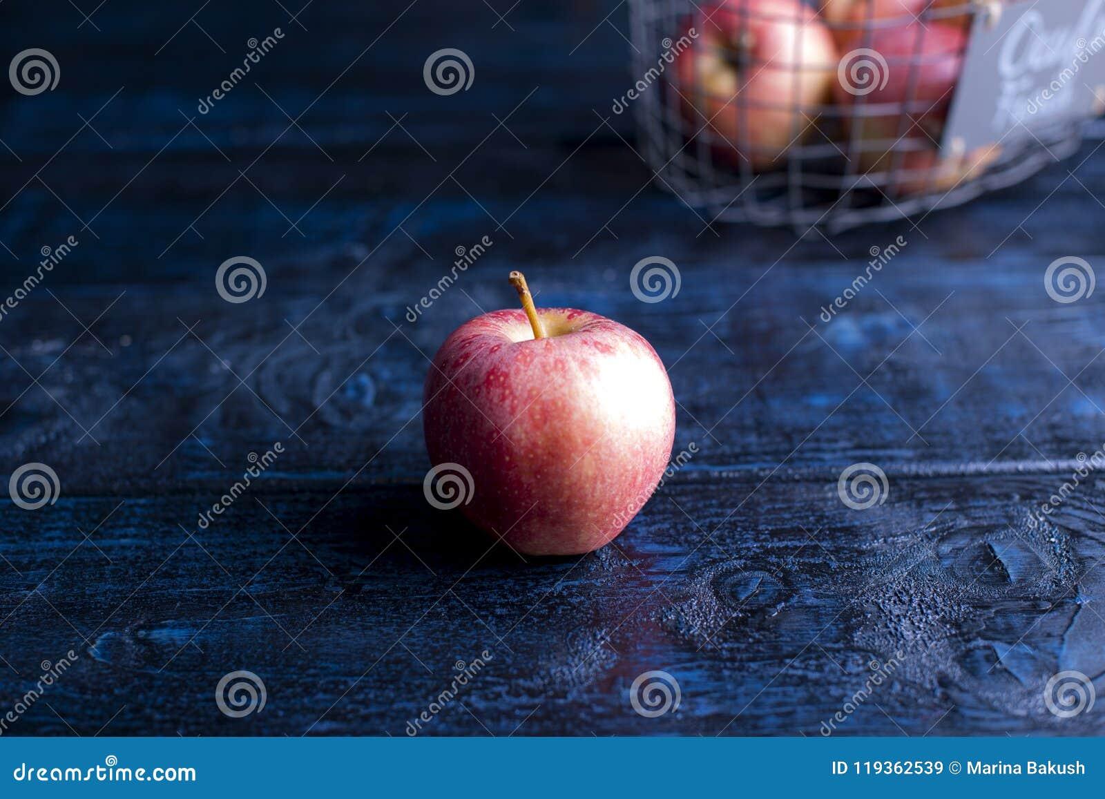 Jeden jabłko na błękitnym tle Uwalnia przestrzeń dla teksta