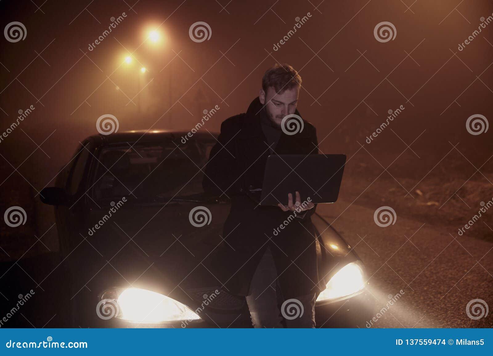 Jeden m?ody cz?owiek u?ywa jego laptop na samochodowym kapiszonie, Ja jest ciemny i nighttime, w obszarze wiejskim