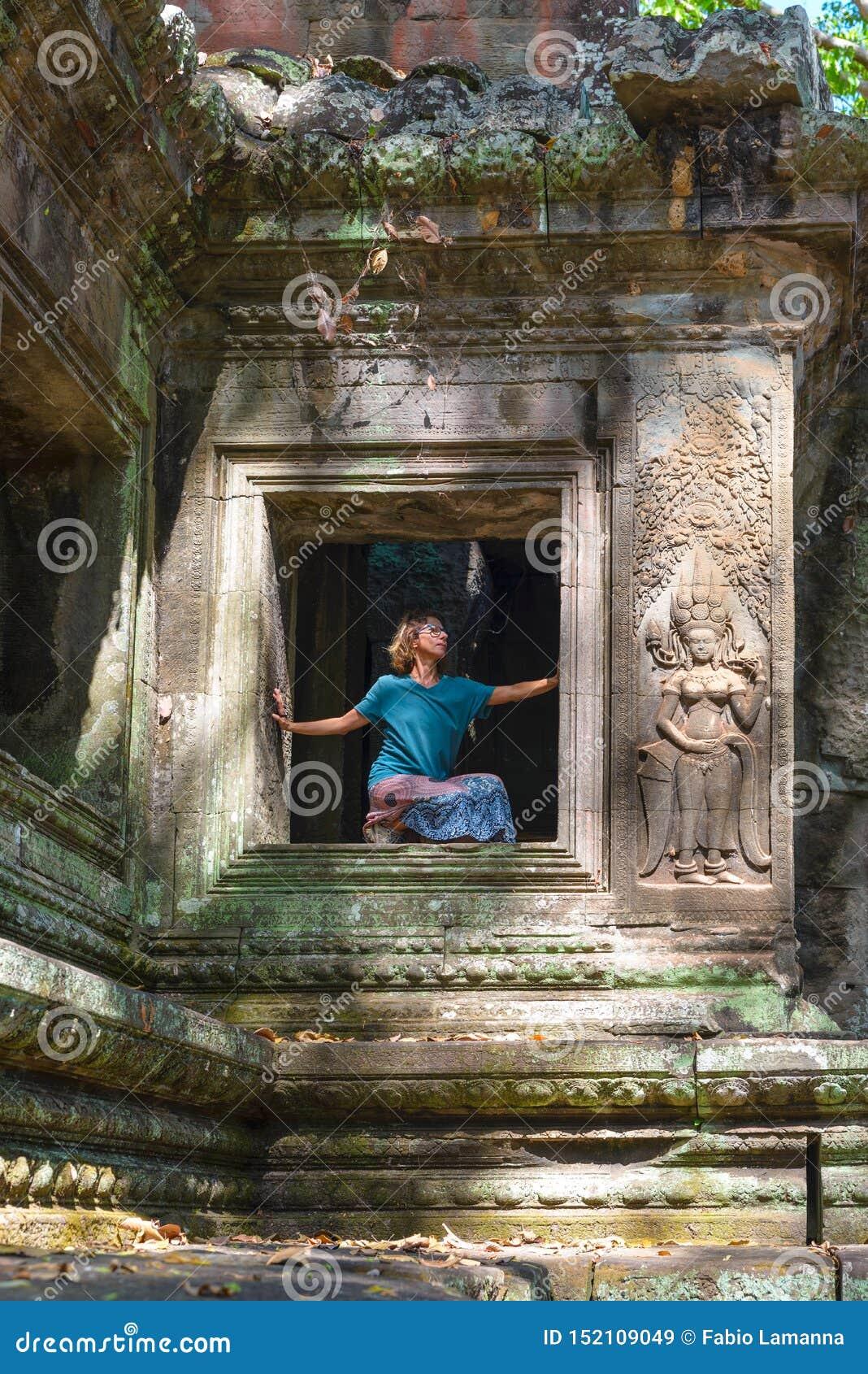Jeden osoba w Angkor Wat ruinach, podr??y miejsce przeznaczenia Kambod?a Kobieta w joga pozycji, rozci?ga nog? i podnosz?c? r?k?,