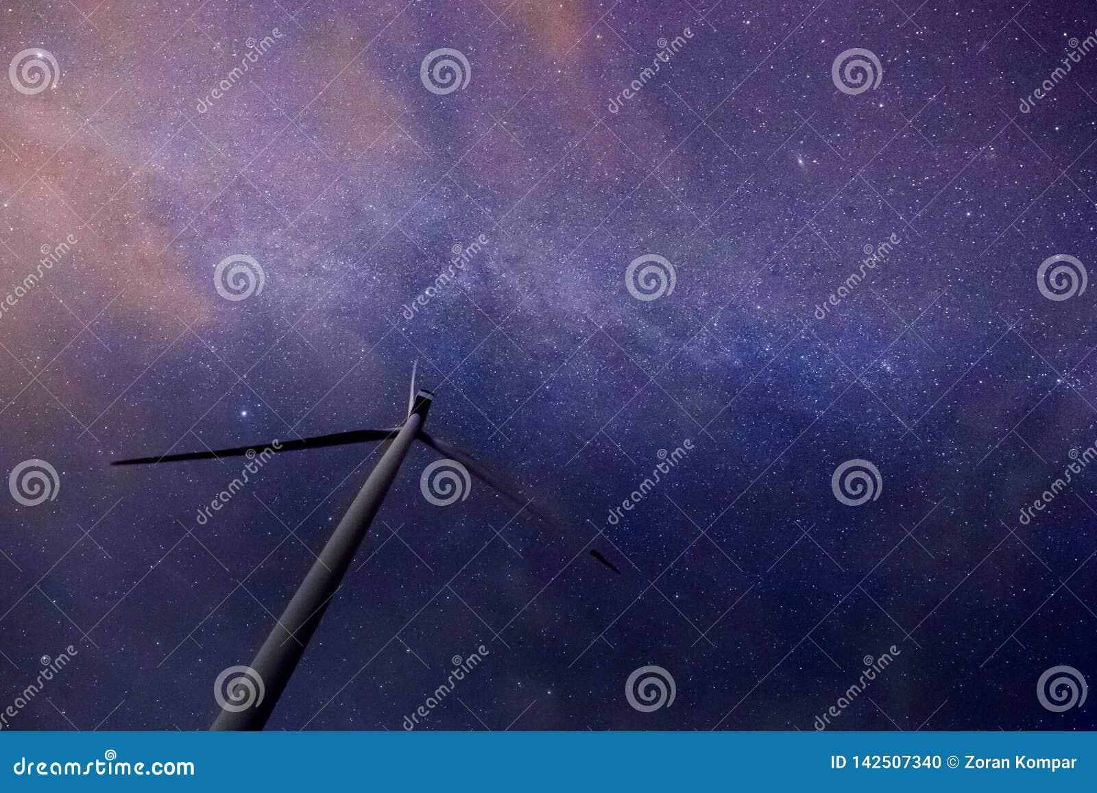 Jeden silnik wiatrowy z piękną drogą mleczną w tle z jaskrawymi gwiazdami nad mieszkanie ziemią przy północą