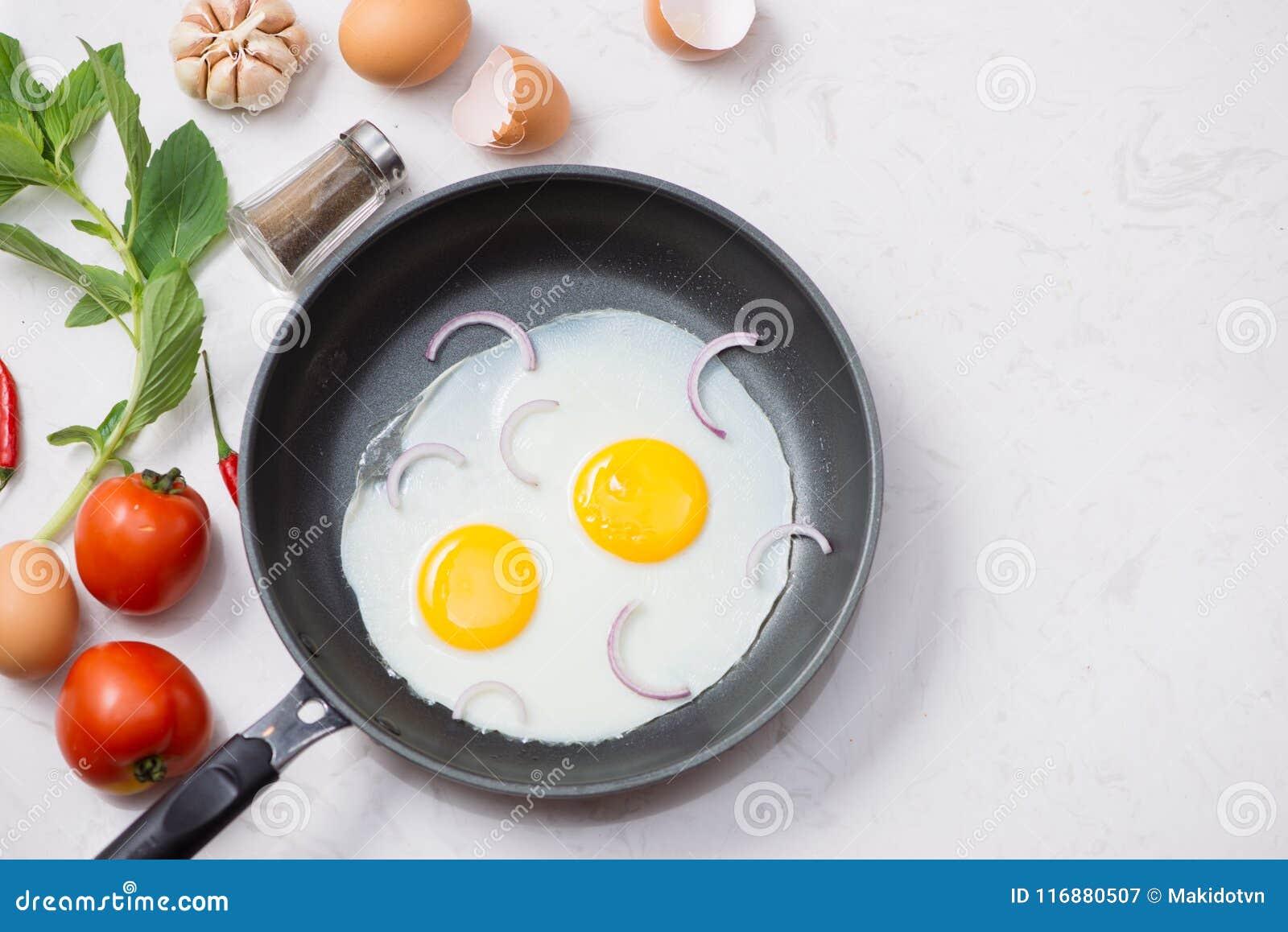 Jedzący w procesie, smażący jajka w smaży niecce dla śniadania