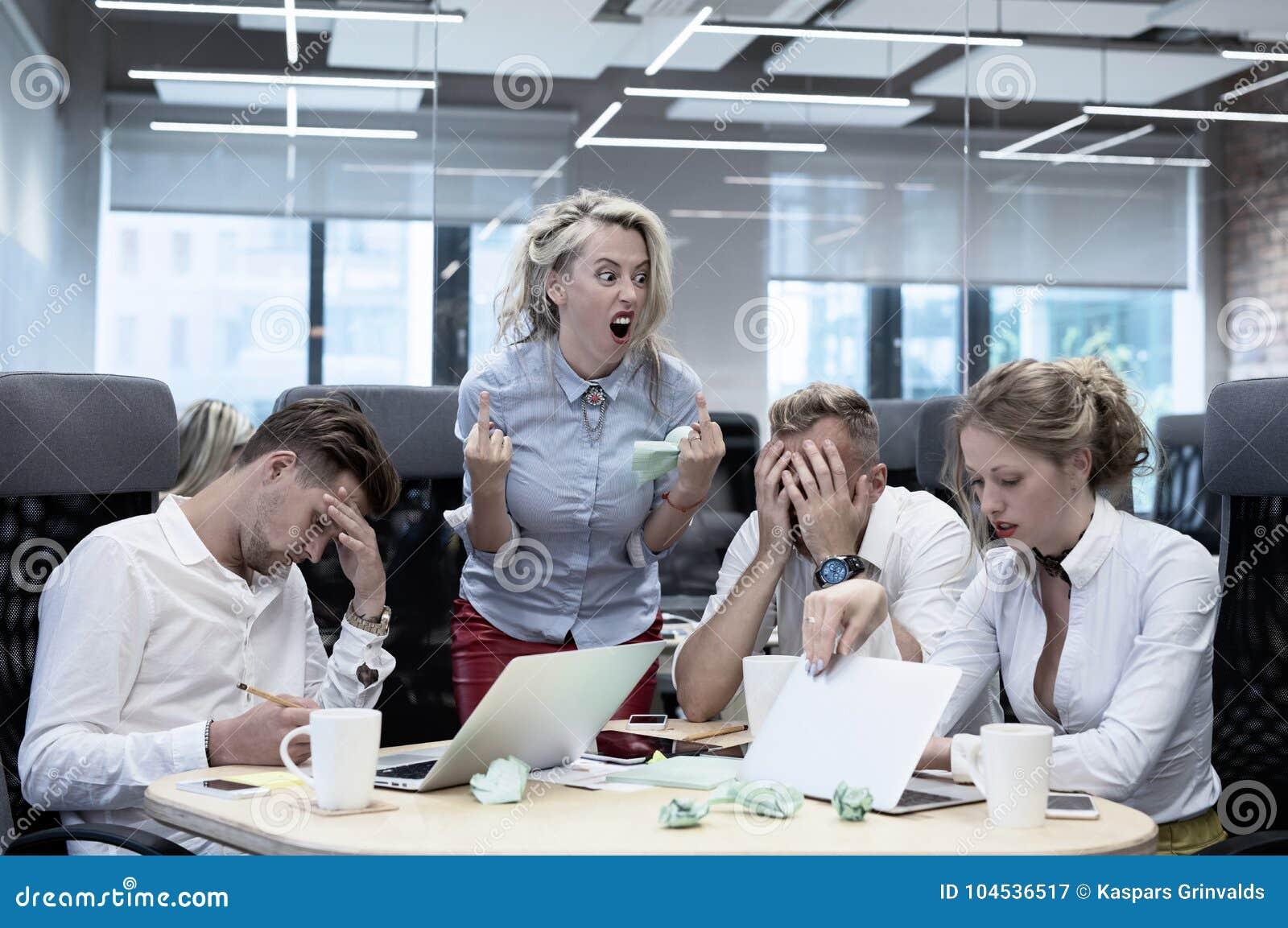 Jefe enojado que muestra gestos a los empleados
