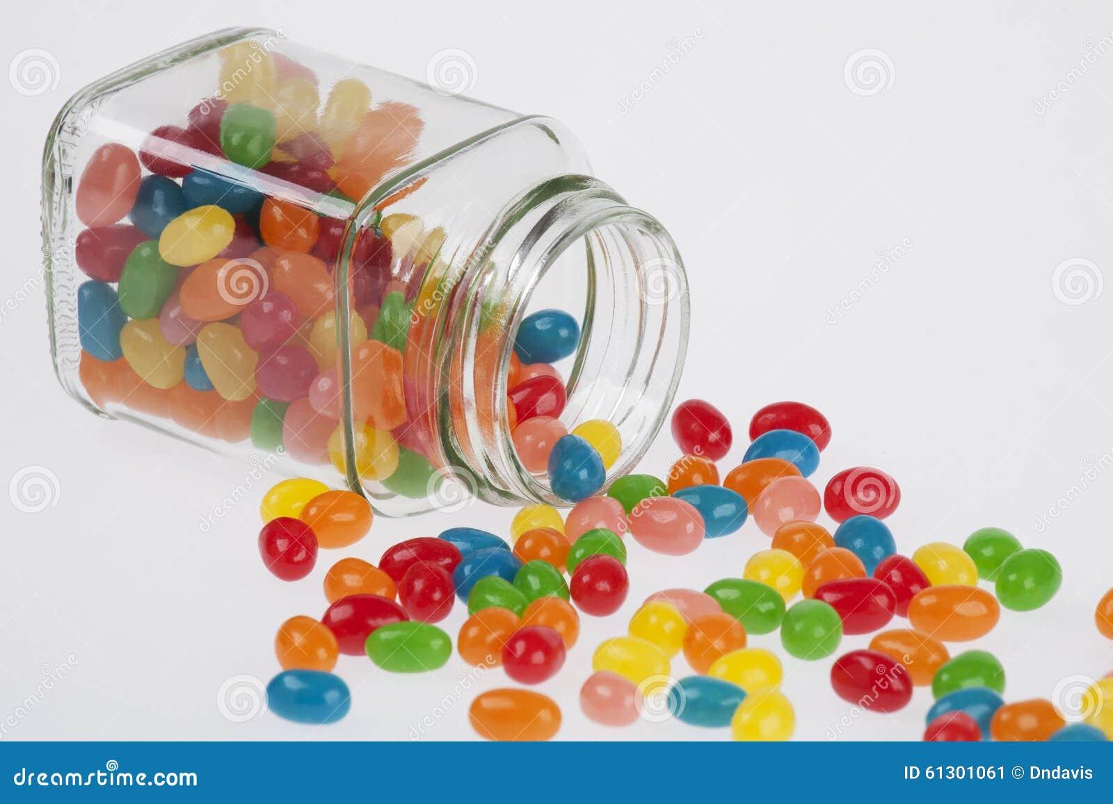 Jelly Beans-Süßigkeit lief Glasgefäß auf weißem backg über