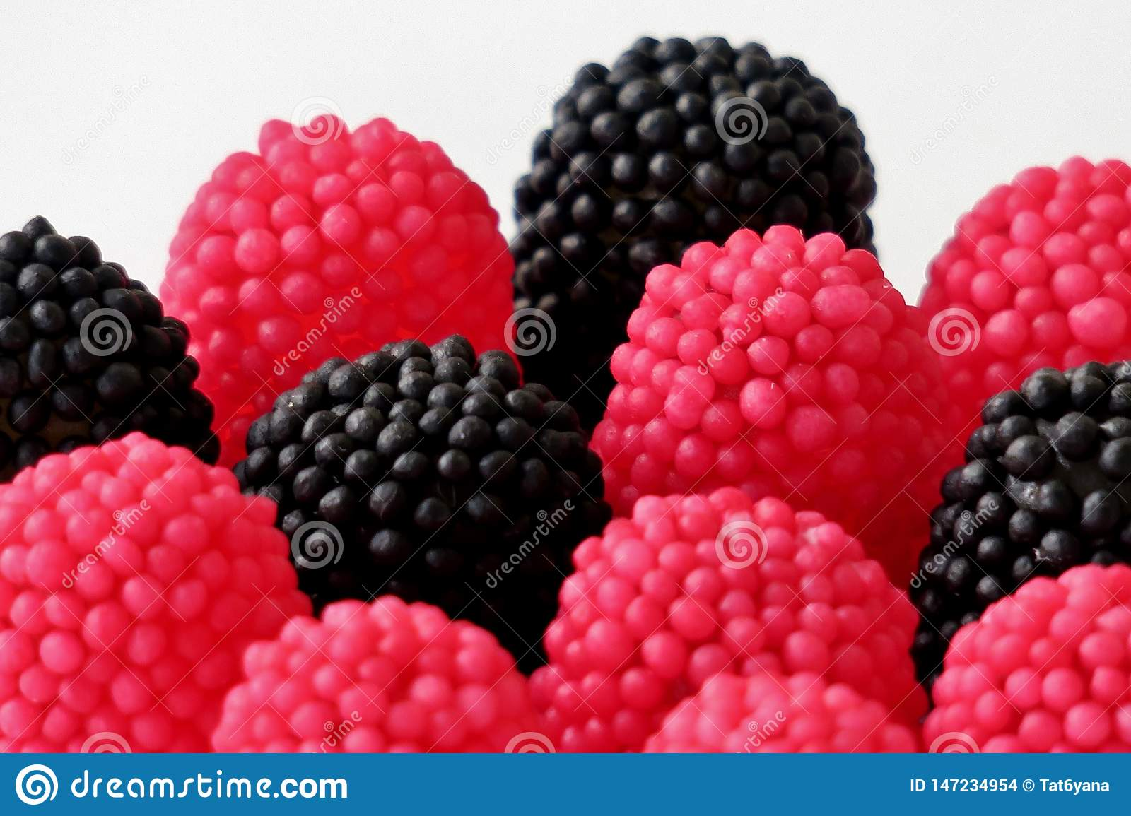 Jelly candies in the form of raspberries, red and black on a white background