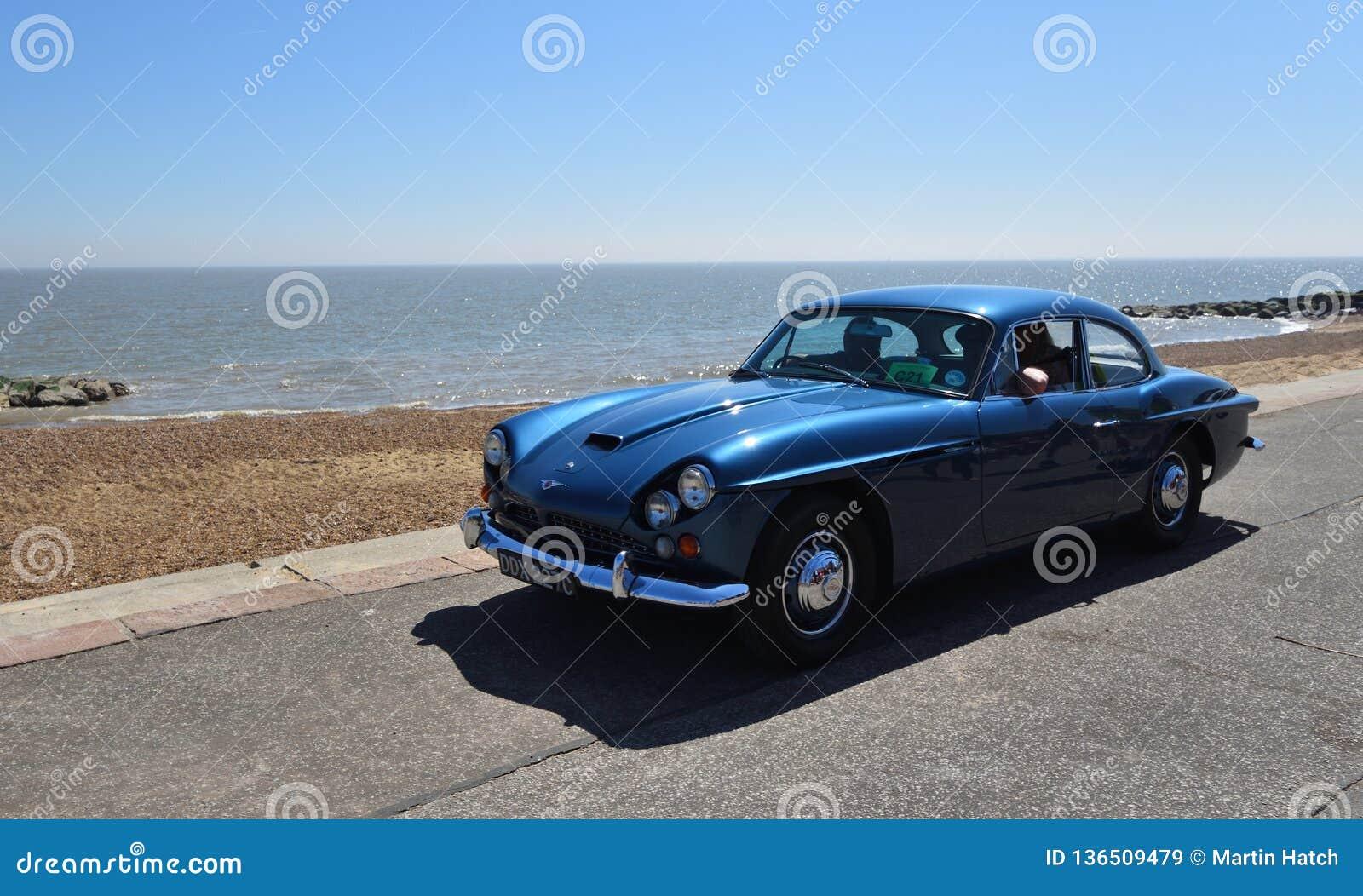 Jensen Motor Car bleu classique étant conduit le long de la promenade de bord de mer