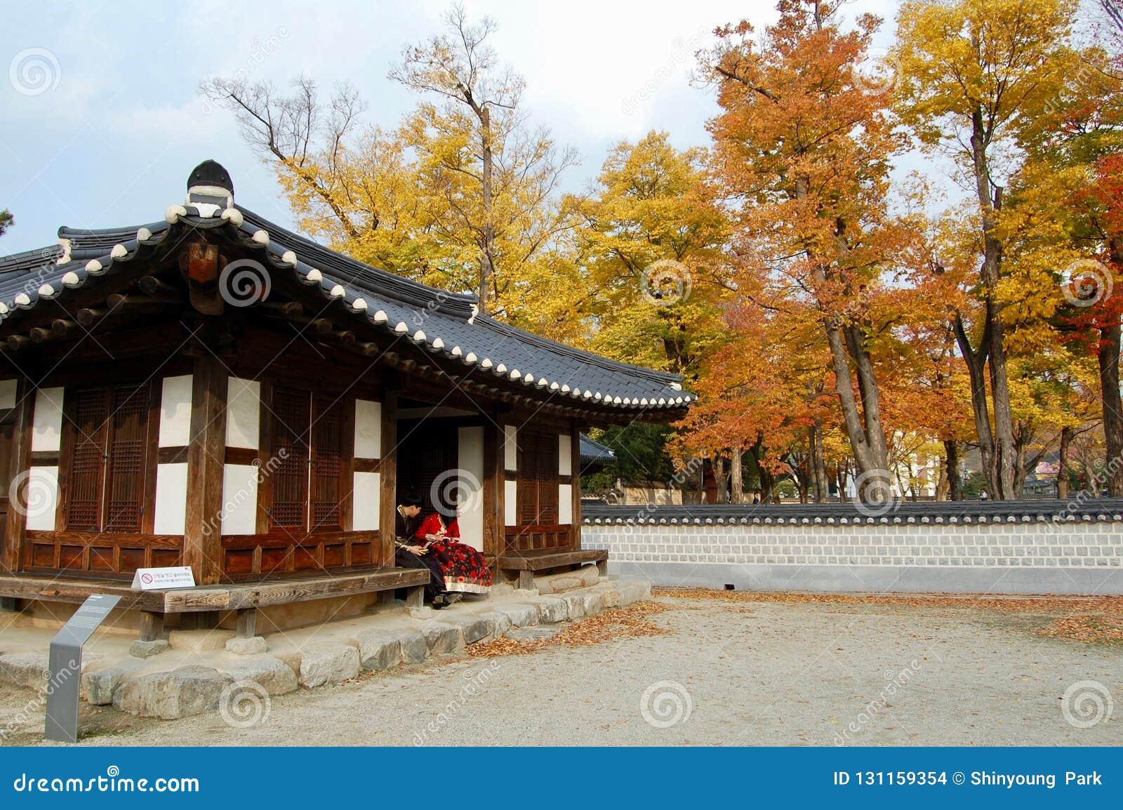 Jeonju Hanok Village, South Korea - 09.11.2018: a couple in hanbok dress inside of traditional palace.
