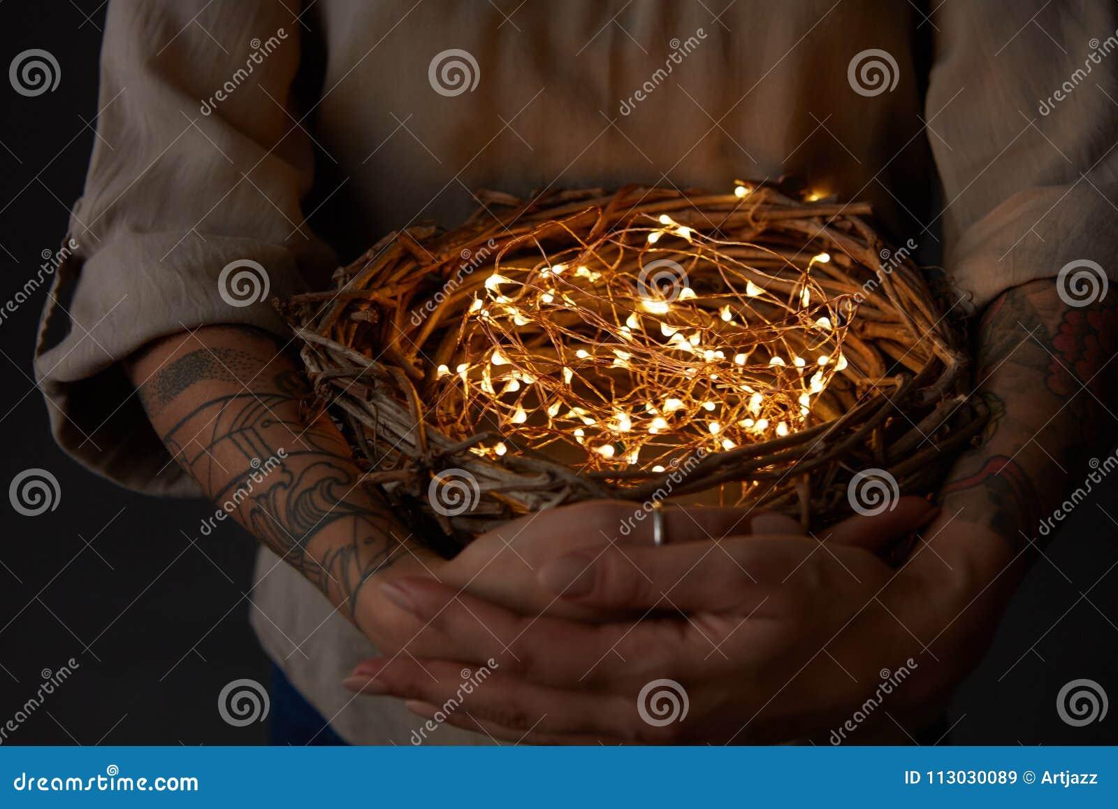 Jerarquice con las luces de la Navidad en las manos de la mujer en fondo negro