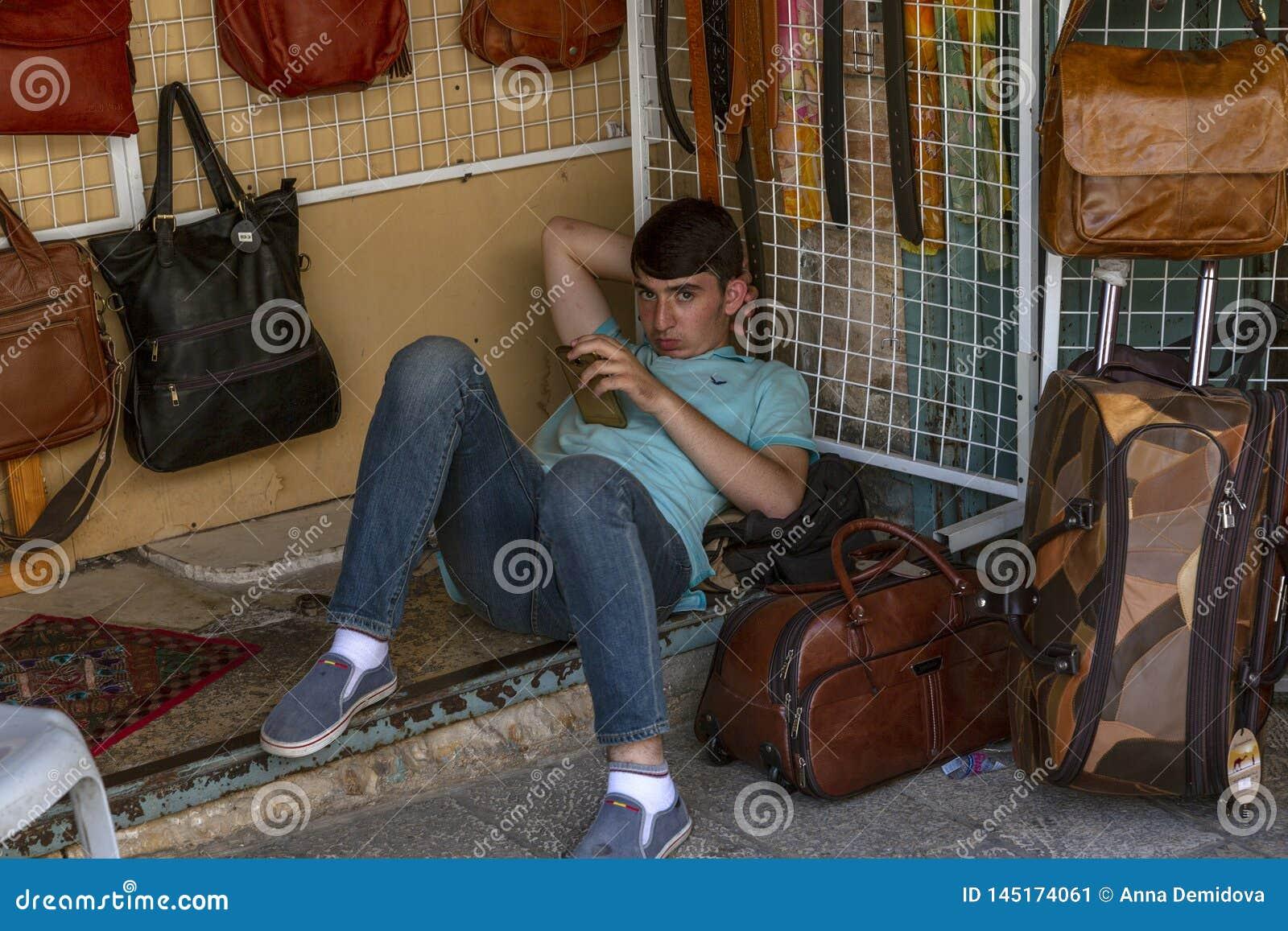 Jerusalém, Israel, 09/11/2016: O menino do vendedor no mercado é descansar, encontrando-se na terra com um telefone