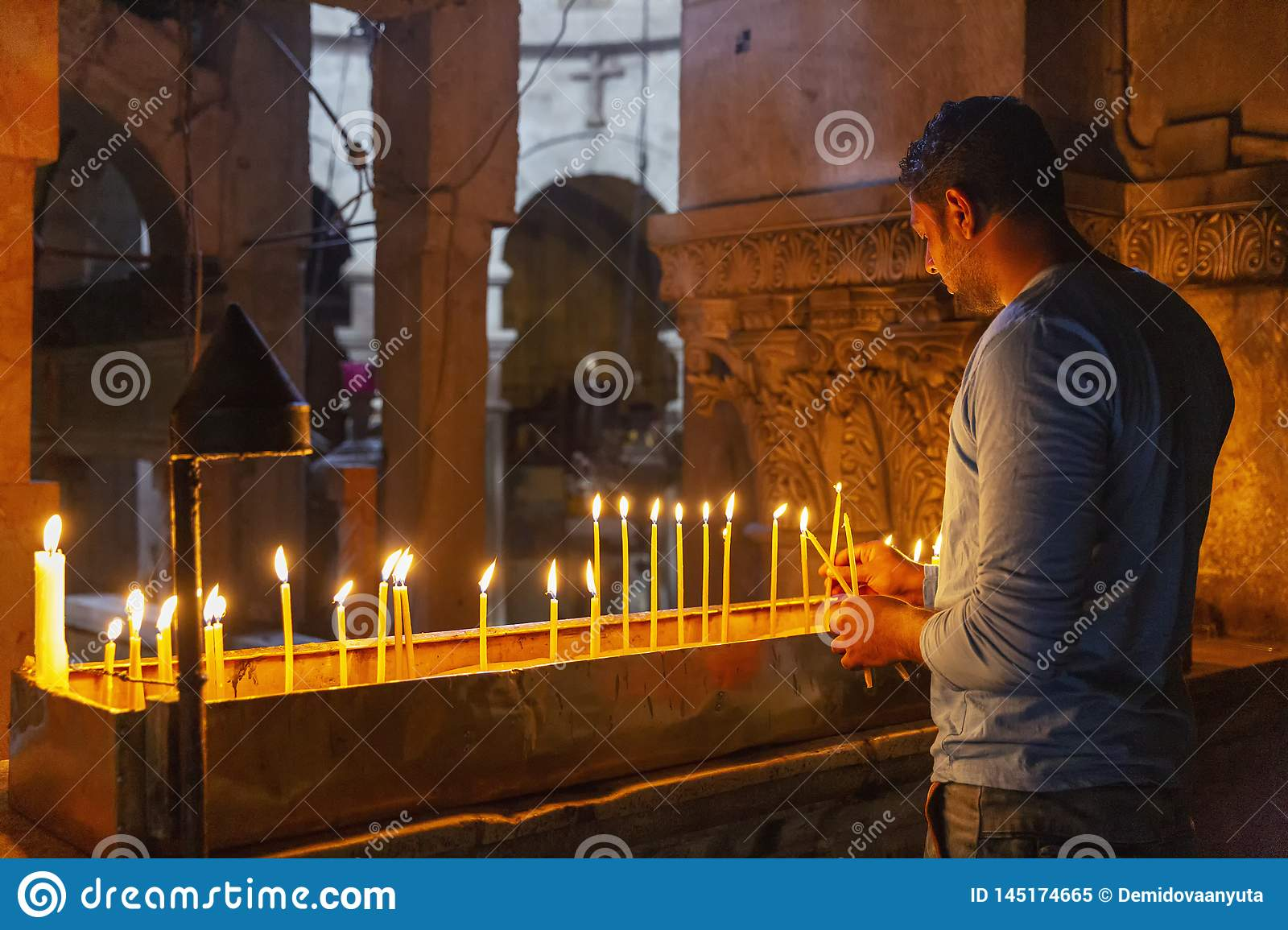Jerusalem, Israel, 09/11/2016: A believing man puts candles and prays in the temple of the Holy Sepulcher