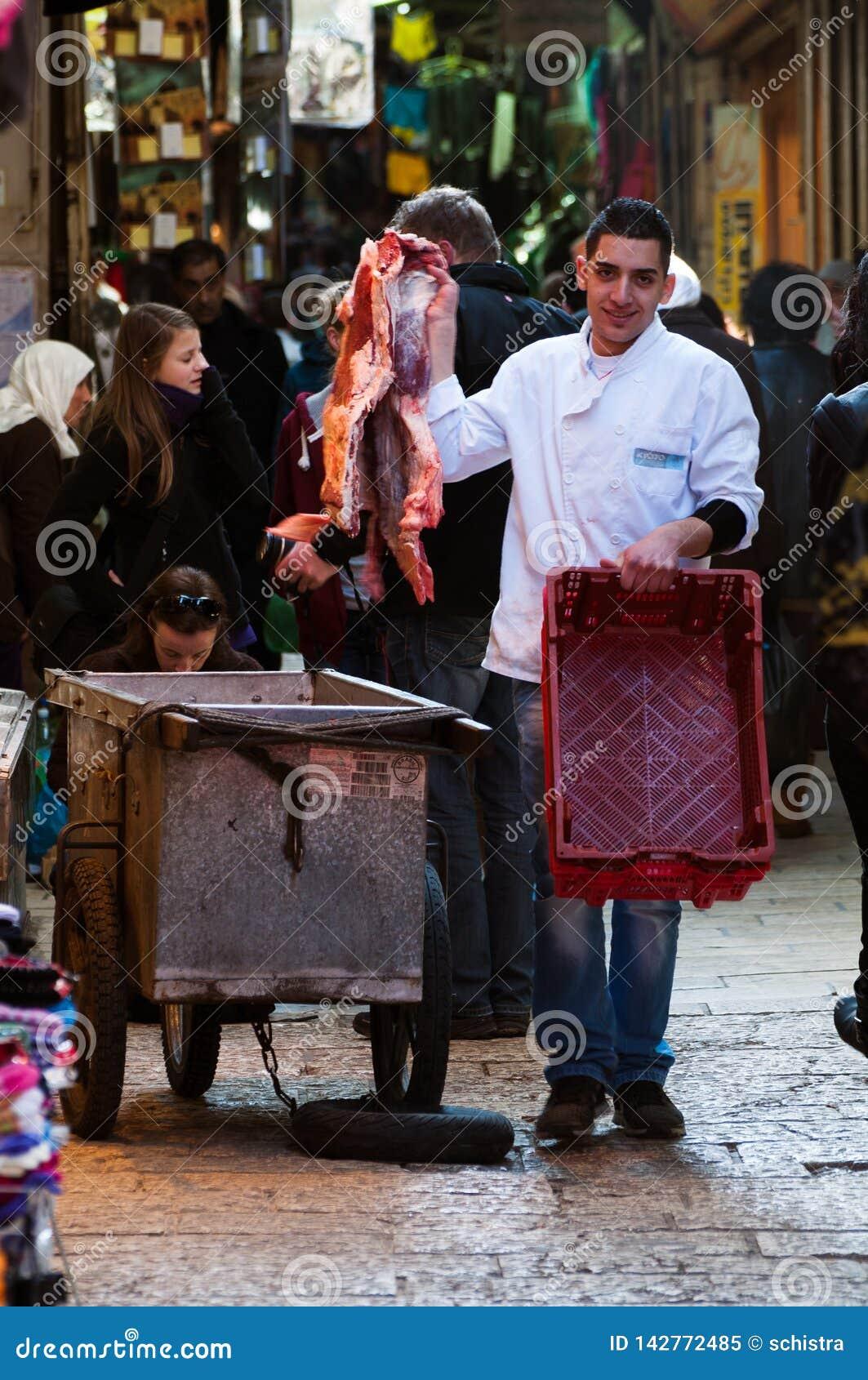 Jeruzalem, December 2012: De jonge slager wisselt vlees in Jeruzalem uit souk
