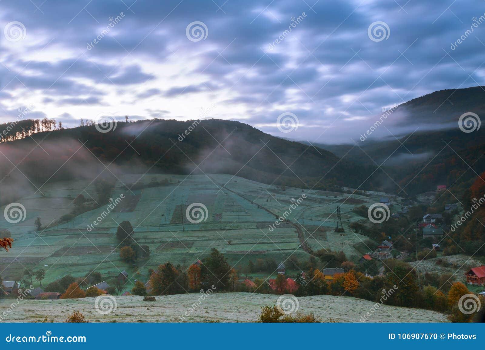 Jesień krajobraz Wioska na Zboczu las w mgle na górach przy nocy księżyc w pełni światłem