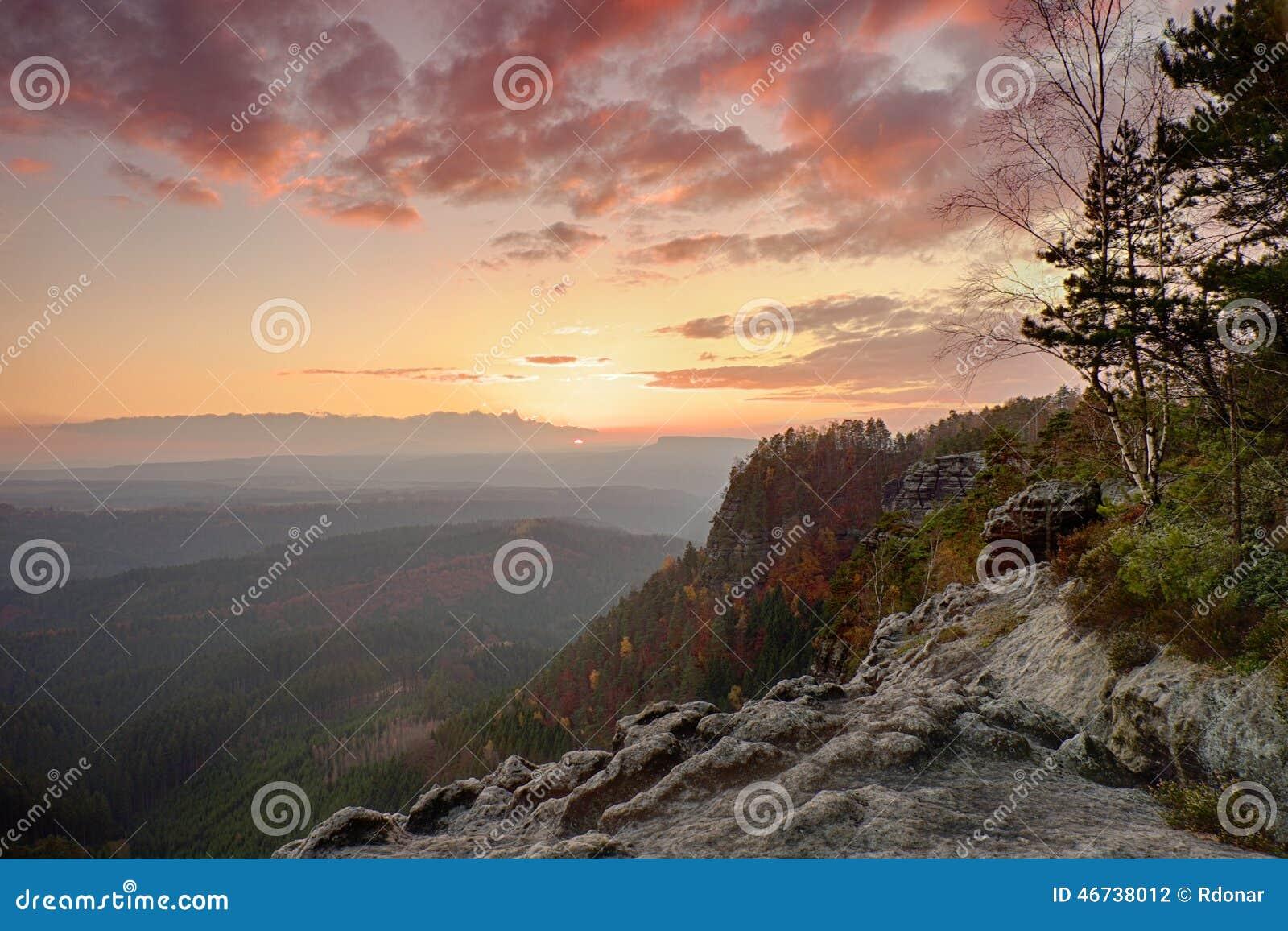 Jesień skalisty krajobraz wśród zmierzchu Kolorowego nieba above głęboki mglisty dolinny pełny wieczór wilgotność Słońce na horyz
