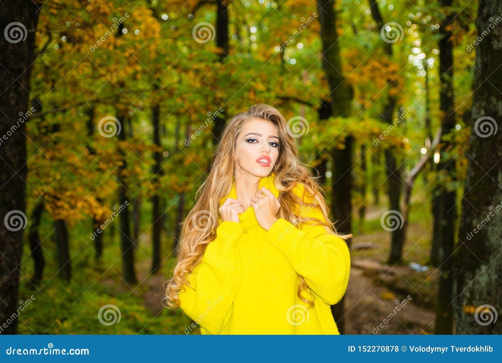 Jesieni kobieta ma zabaw? przy ono u?miecha si? i parkiem Beztroska m?oda kobieta w modnego rocznika czerwonym pulowerze lub pulo