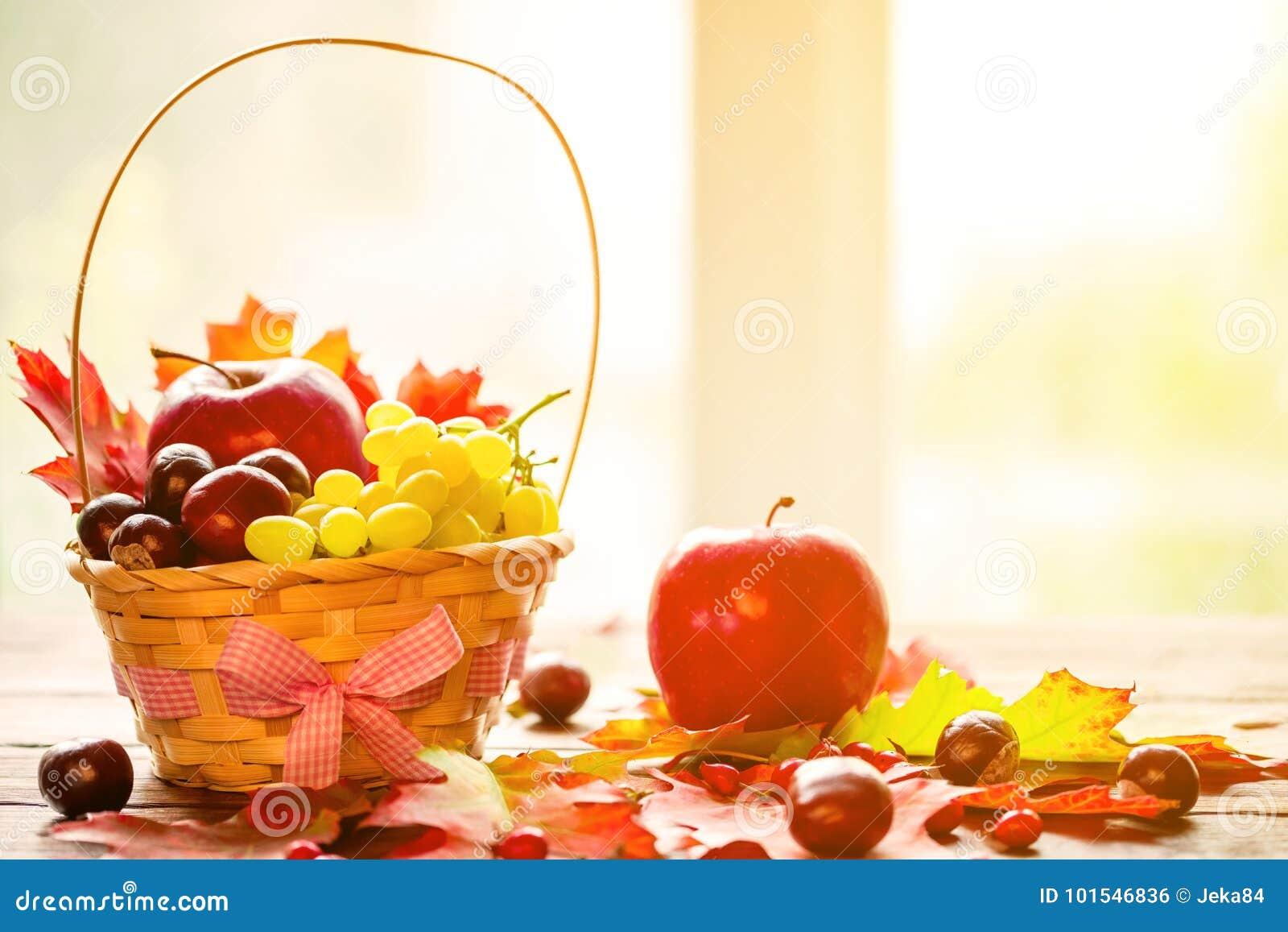 Jesieni tło z koszem z żółtymi liśćmi klonowymi, winogrona, czerwoni jabłka Rama spadku żniwo na starzejącym się drewnie z kopii