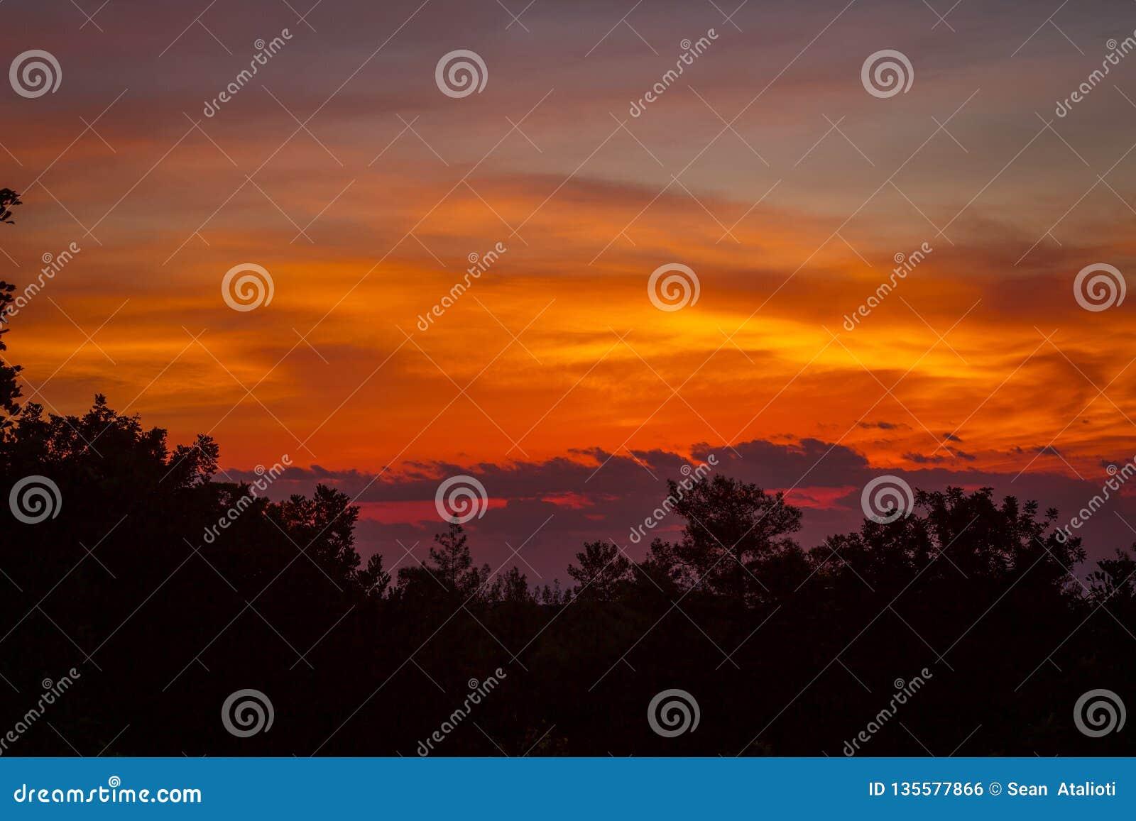 Jesieni jesieni wieczór nieba, Piękny pomarańczowy słońce ustawiający nad pokojowymi górami