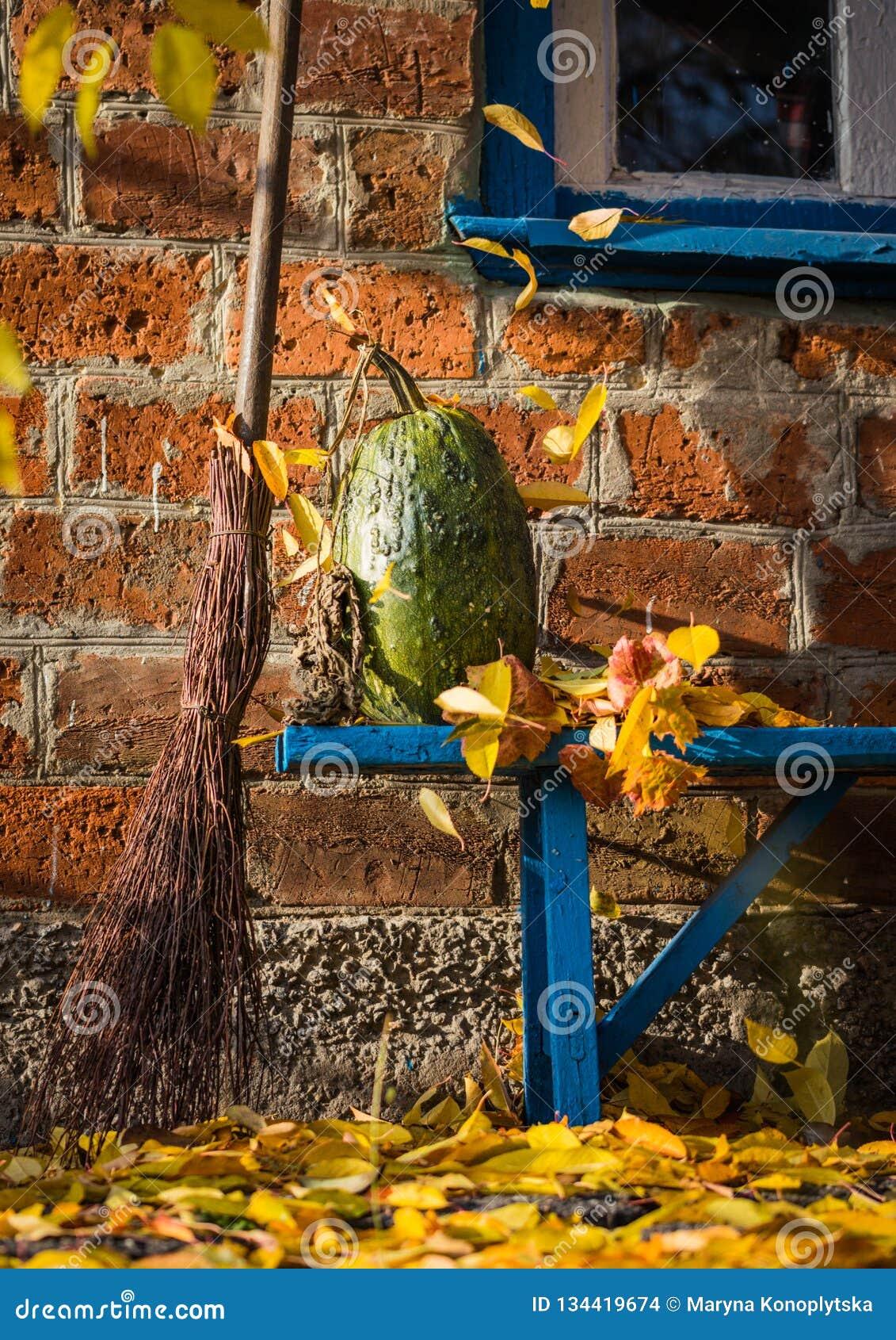 Jesieni wioski podwórze Bania, żółty ulistnienie i stara miotła na tle ceglany dom,