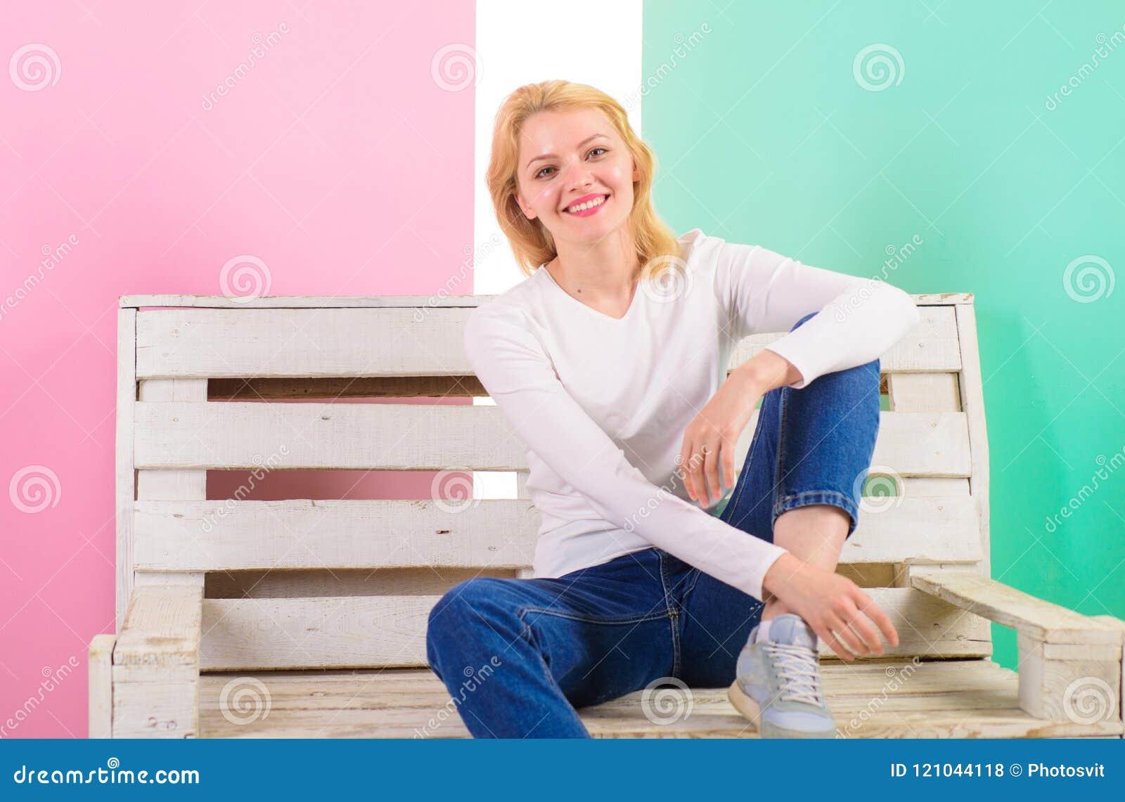 Jest po prostu wspaniała Piękny młoda kobieta uśmiech podczas gdy siedzący na ławce przeciw różowemu tłu Dziewczyna woli