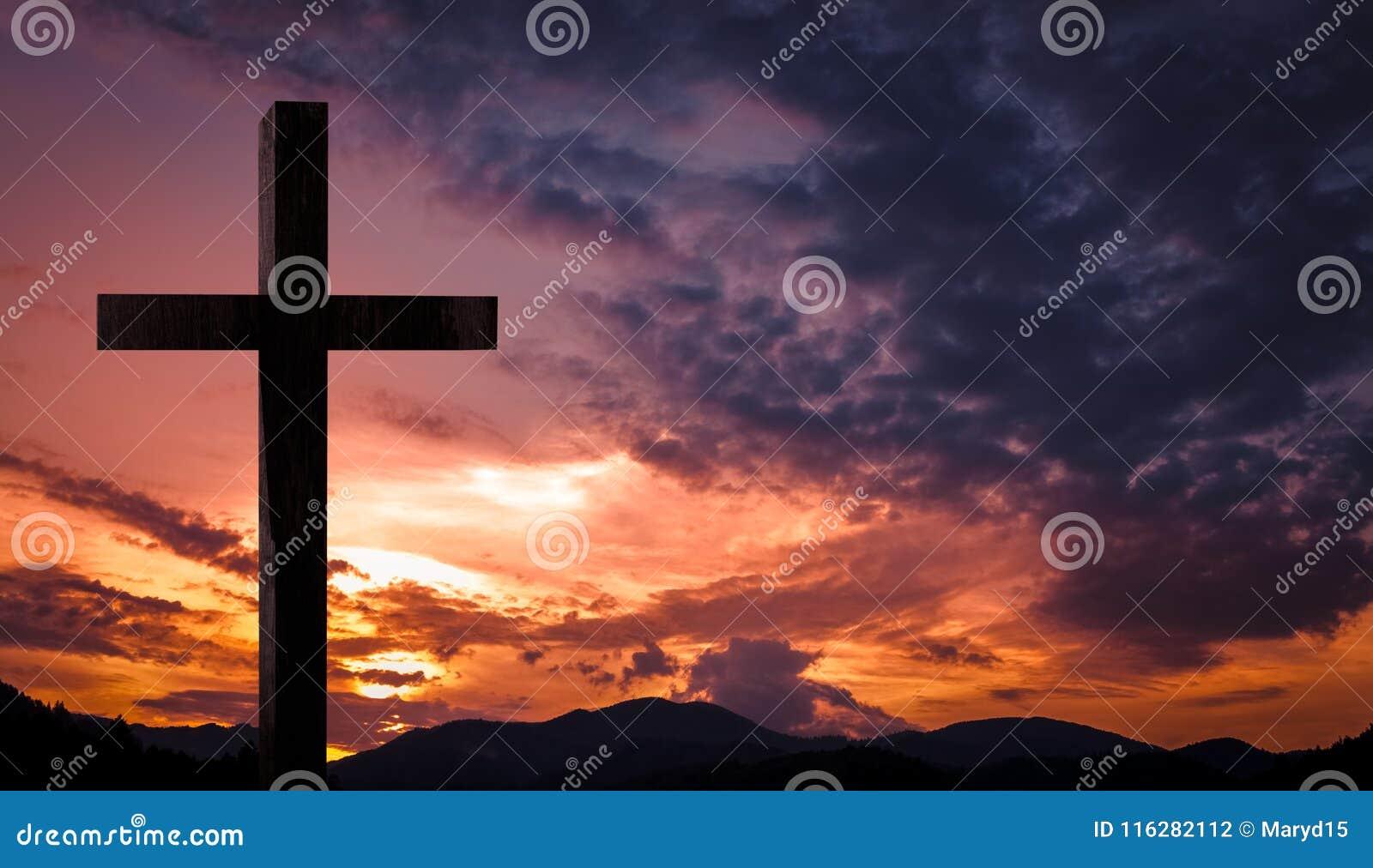 Jesus Christ cruza-se, crucifixo de madeira em um fundo celestial com luz dramática e nuvens e por do sol alaranjado colorido