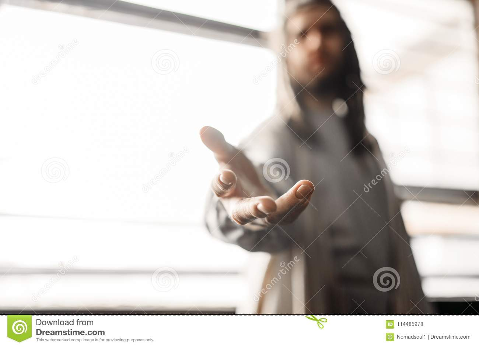 Jesus Christ in der weißen Robe, die heraus seine Hand erreicht