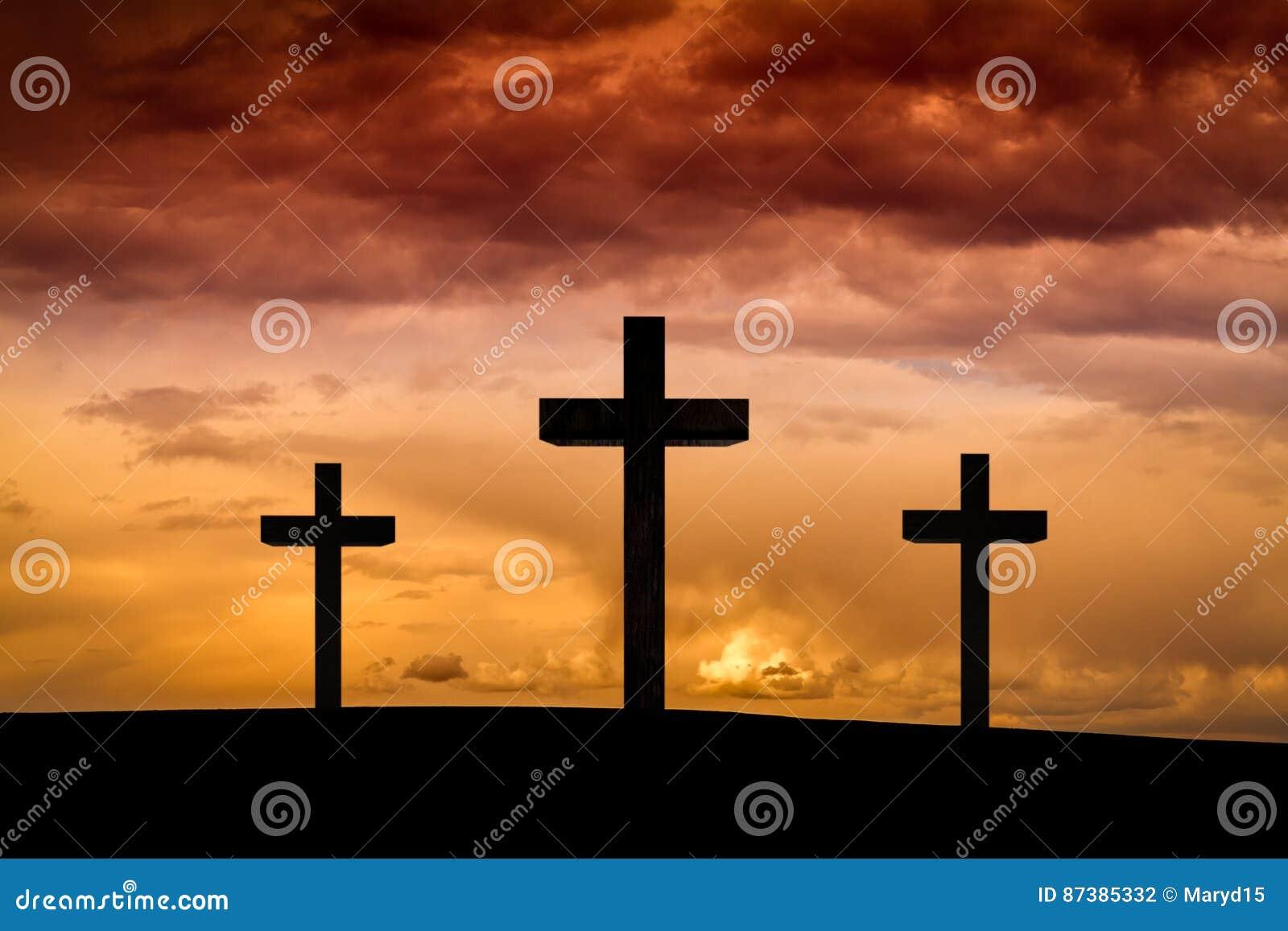 Jesus Christ-Kreuz auf einem roten, orange Himmel mit drastischen Wolken, dunkler Sonnenuntergang