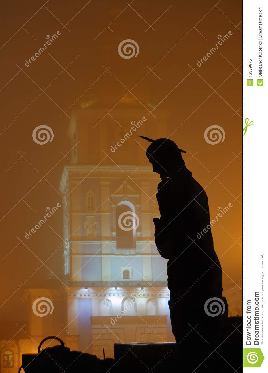Silhouette of a sculpture of Jesus against a monastery belltower ...