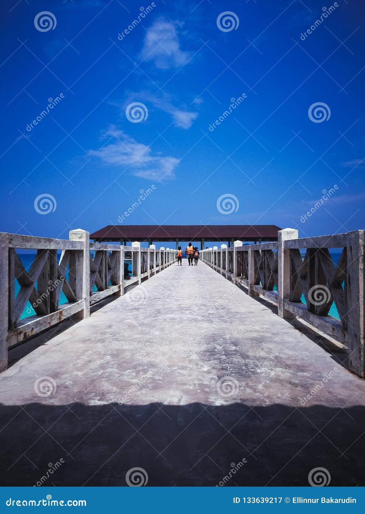 Jetée en bois dans le midi sous les cieux bleus clairs avec la marche de personnes