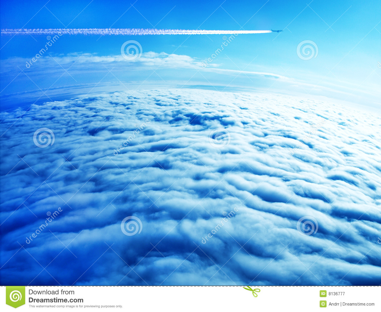 Jet plane contrail in blue sky above the clouds