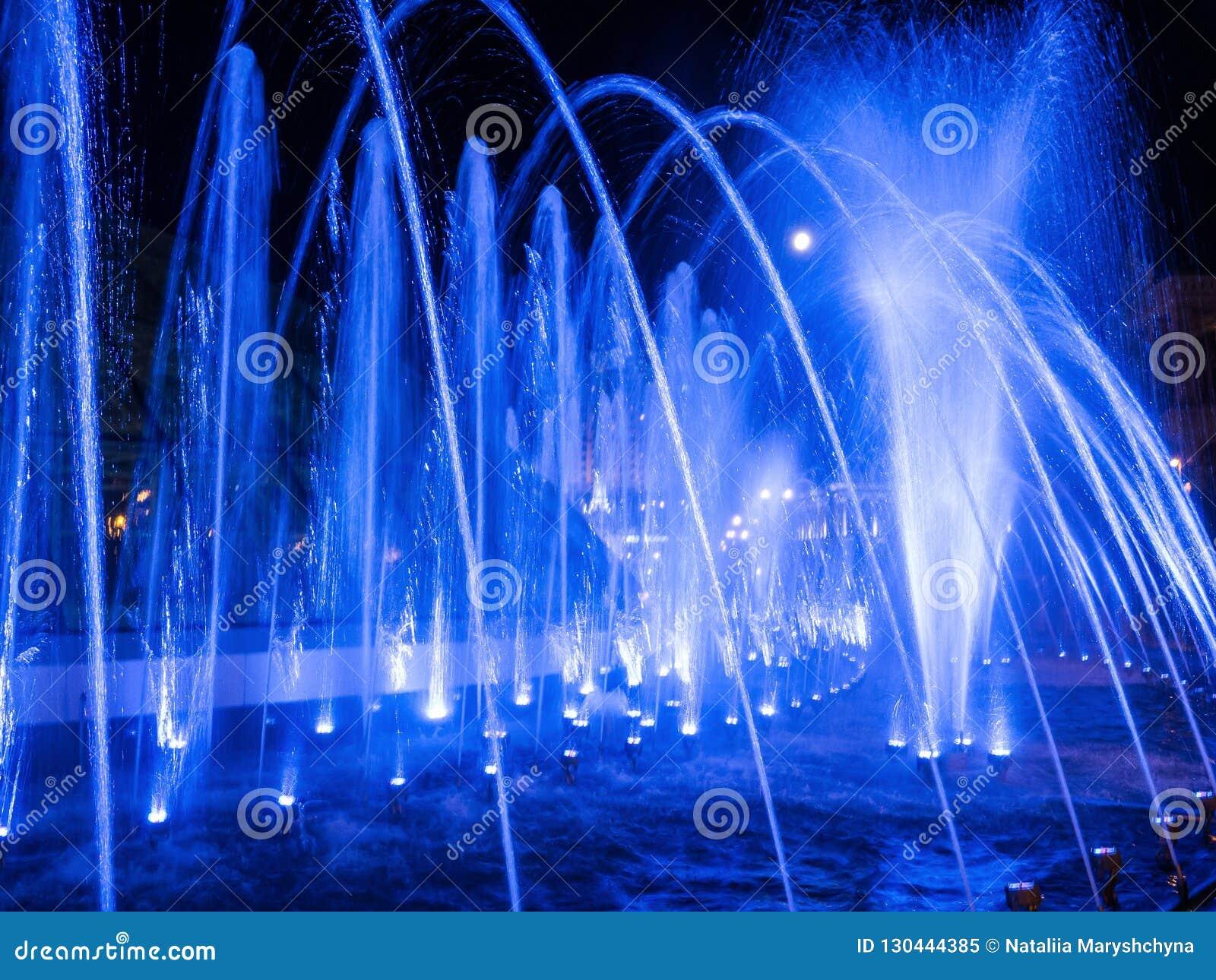 Jets d eau colorés dans la fontaine la nuit avec la pleine lune