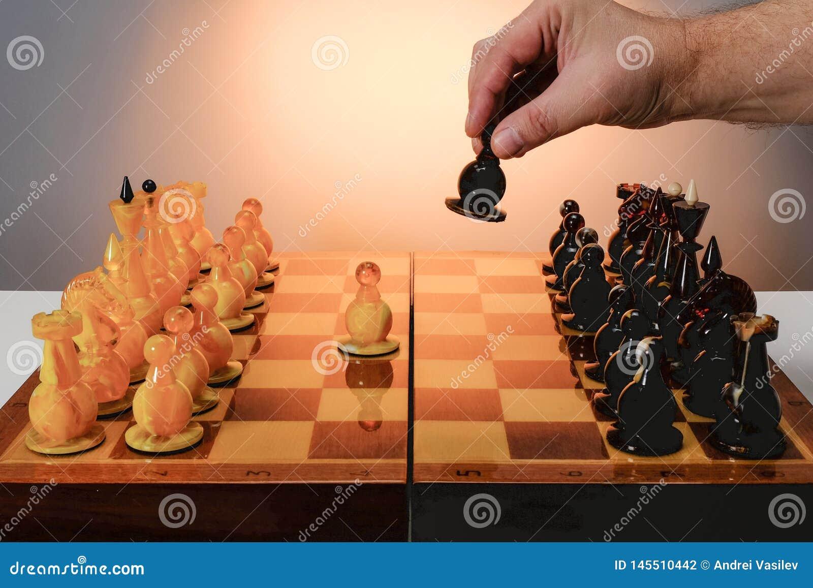 Jeu d ?checs avec les pi?ces d ?checs ambres sur le conseil Main de joueur tenant le gage noir Avec le fond d or de gradient
