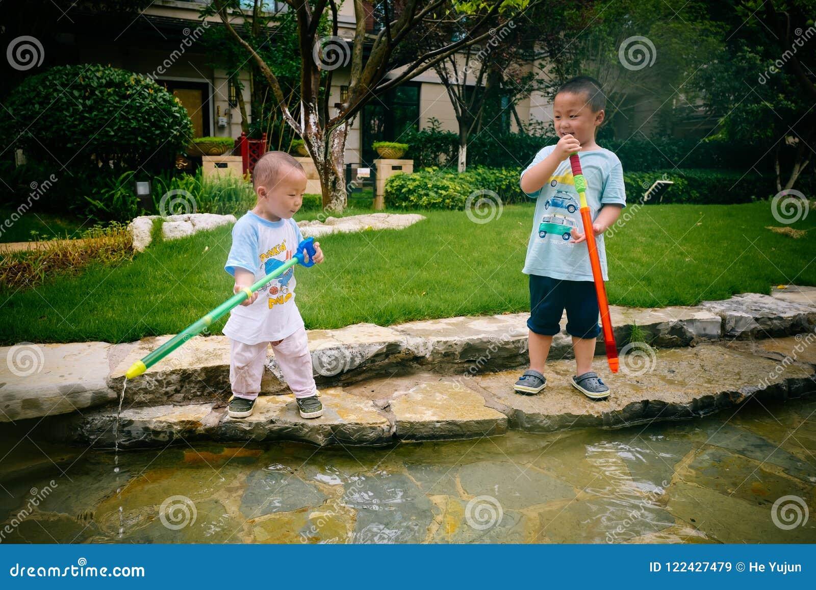 Jeu d enfants dans le jardin avec des armes à feu et des fusils de l eau