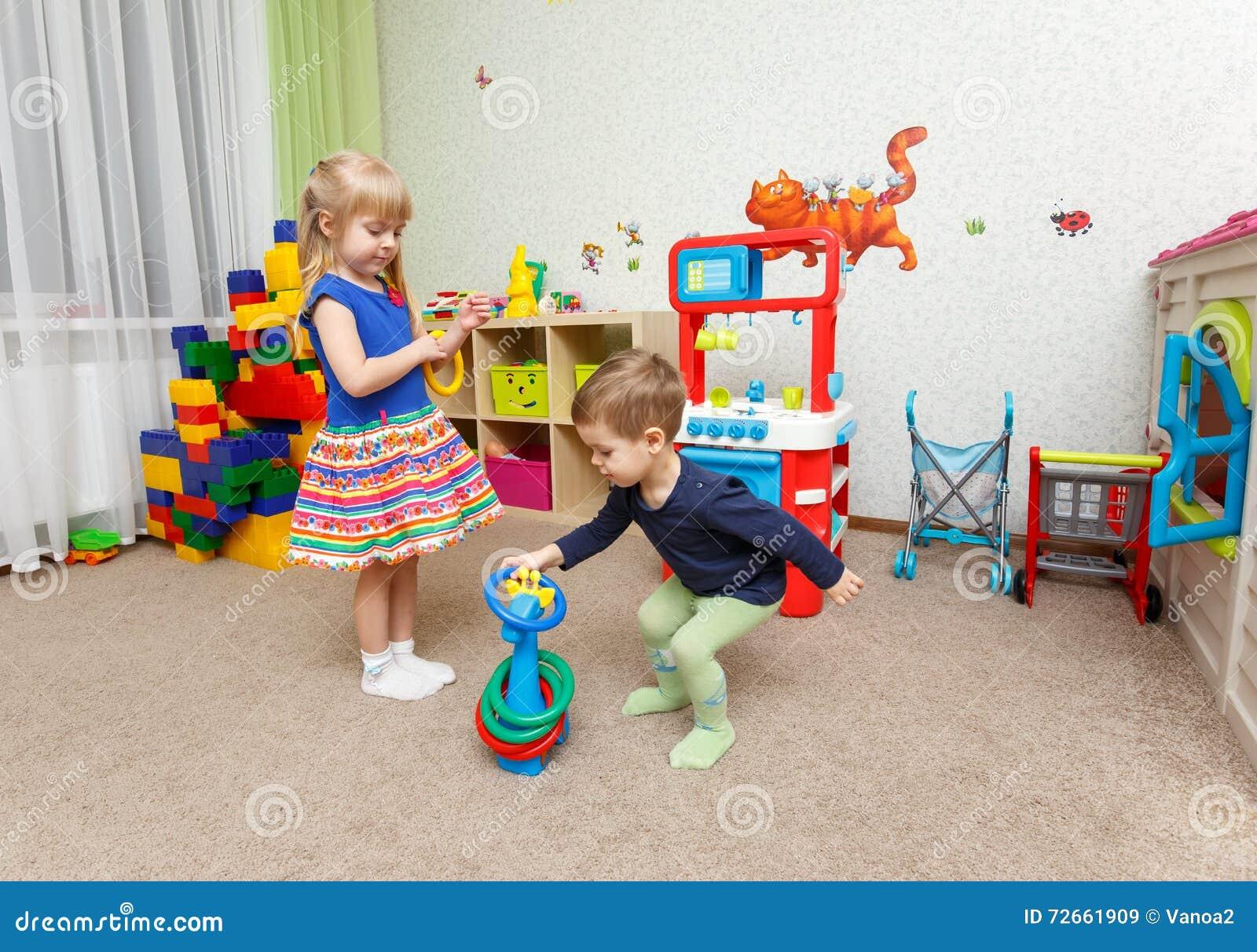 Jeu de deux enfants avec les anneaux en plastique dans le jardin d enfants