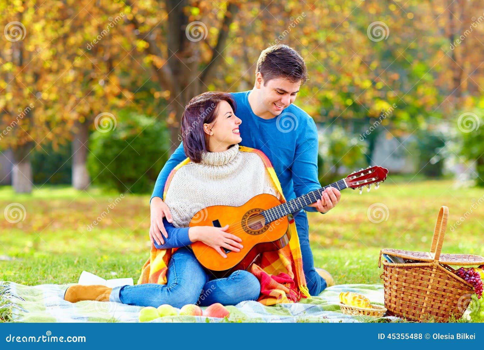 Jeu de enseignement de fille d homme une guitare sur le pique-nique d automne