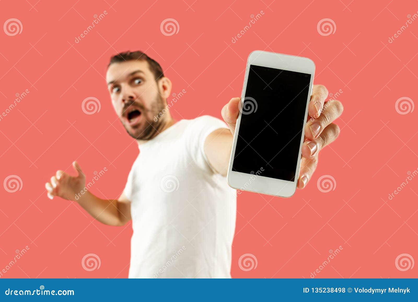 Jeune écran bel de smartphone d apparence d homme d isolement sur le fond de corail dans le choc avec un visage de surprise