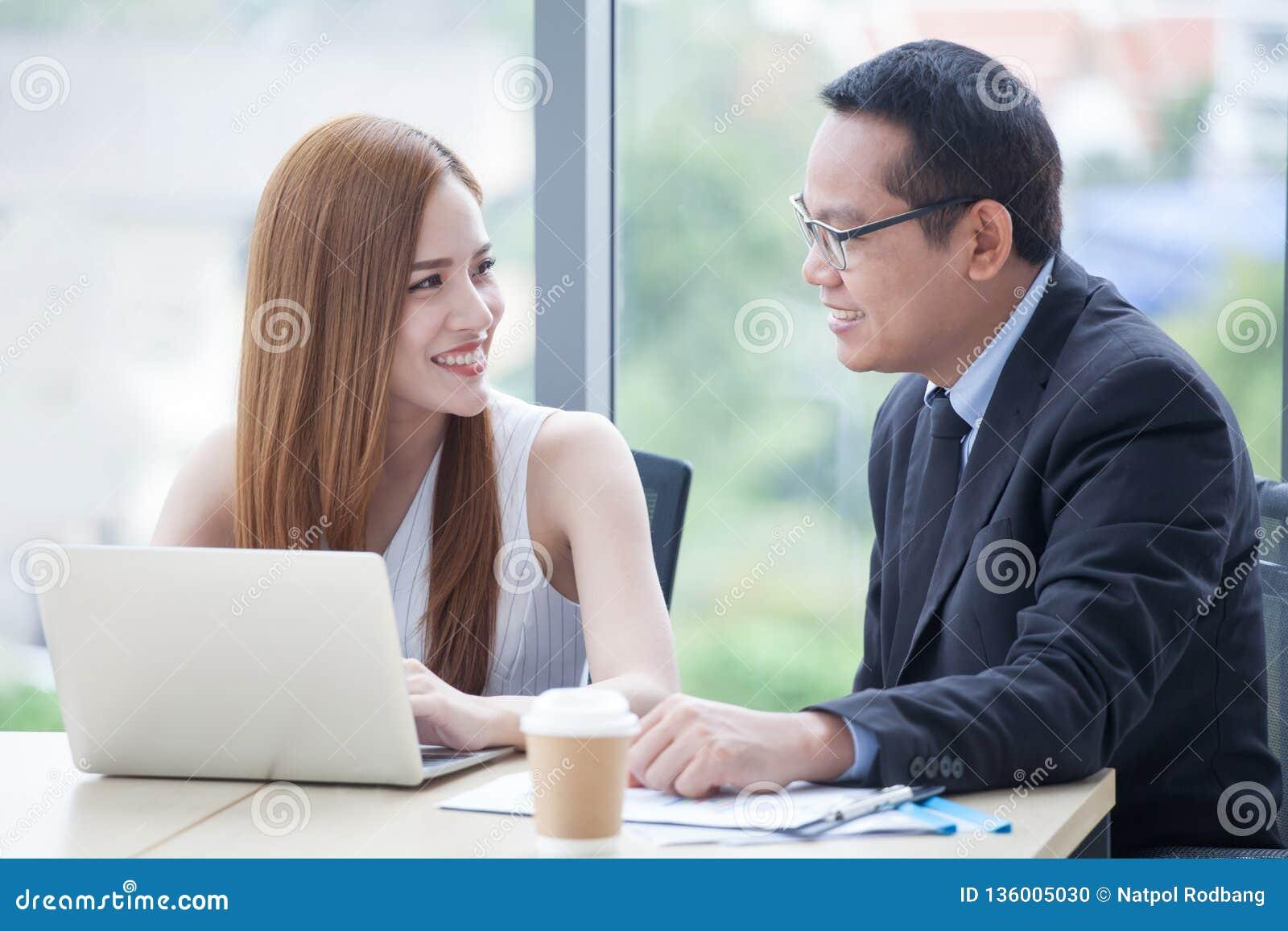 Jeune équipe heureuse d homme d affaires et de femme d affaires collaborant avec l ordinateur portable sur le bureau discutant l