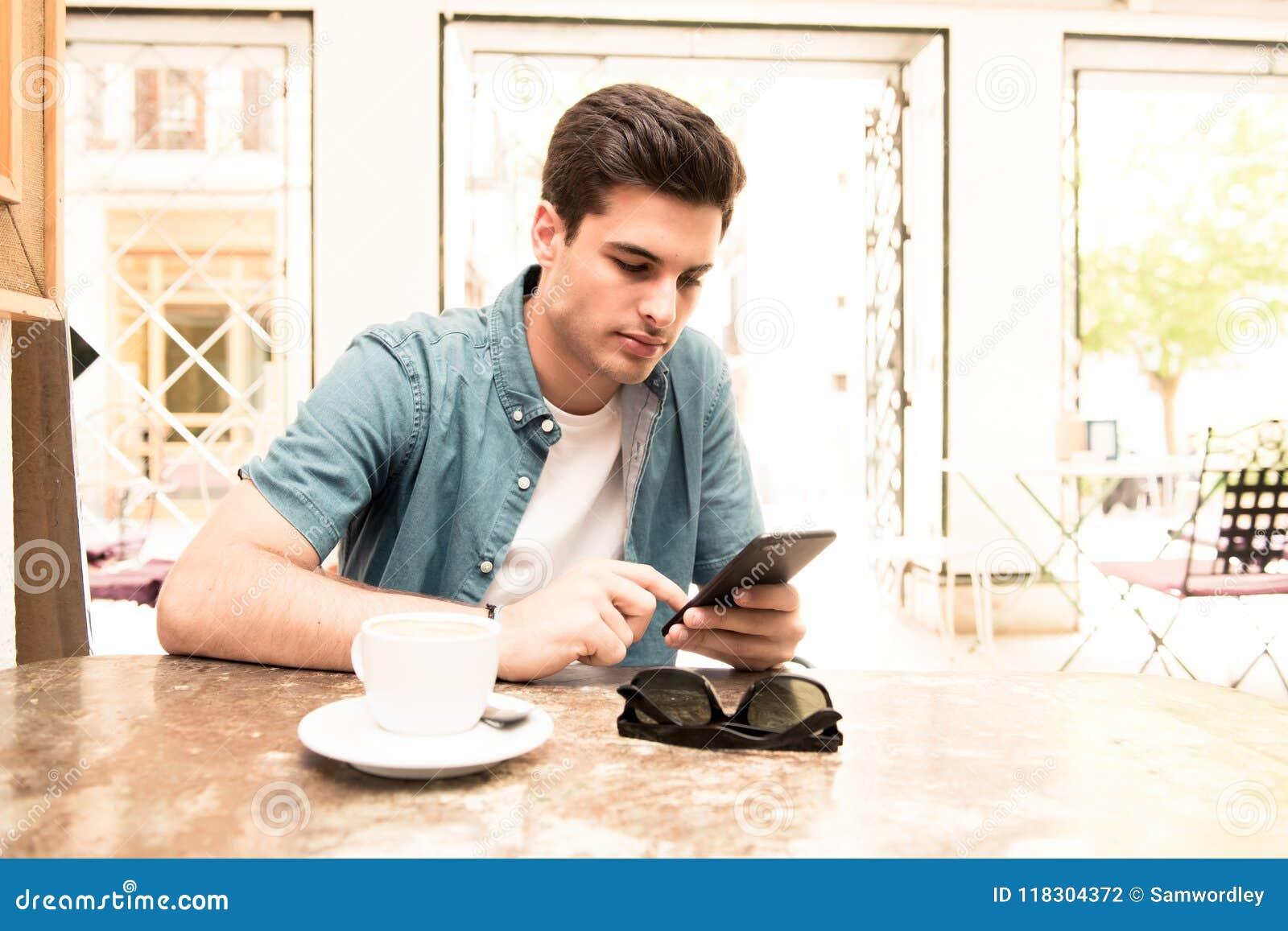Jeune étudiant à l aide de son téléphone intelligent pour lire le texte tout en ayant un café