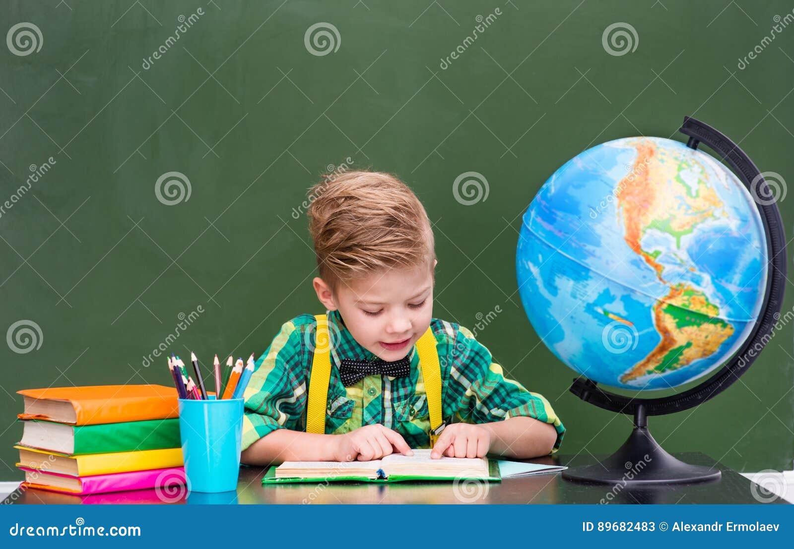 Jeune étudiant lisant un livre près du tableau vert vide