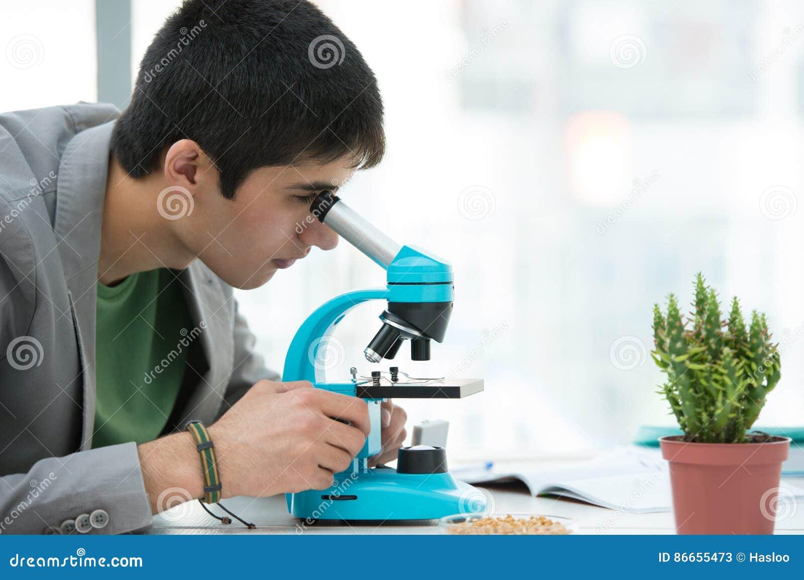 Jeune étudiant masculin bel à l aide du microscope