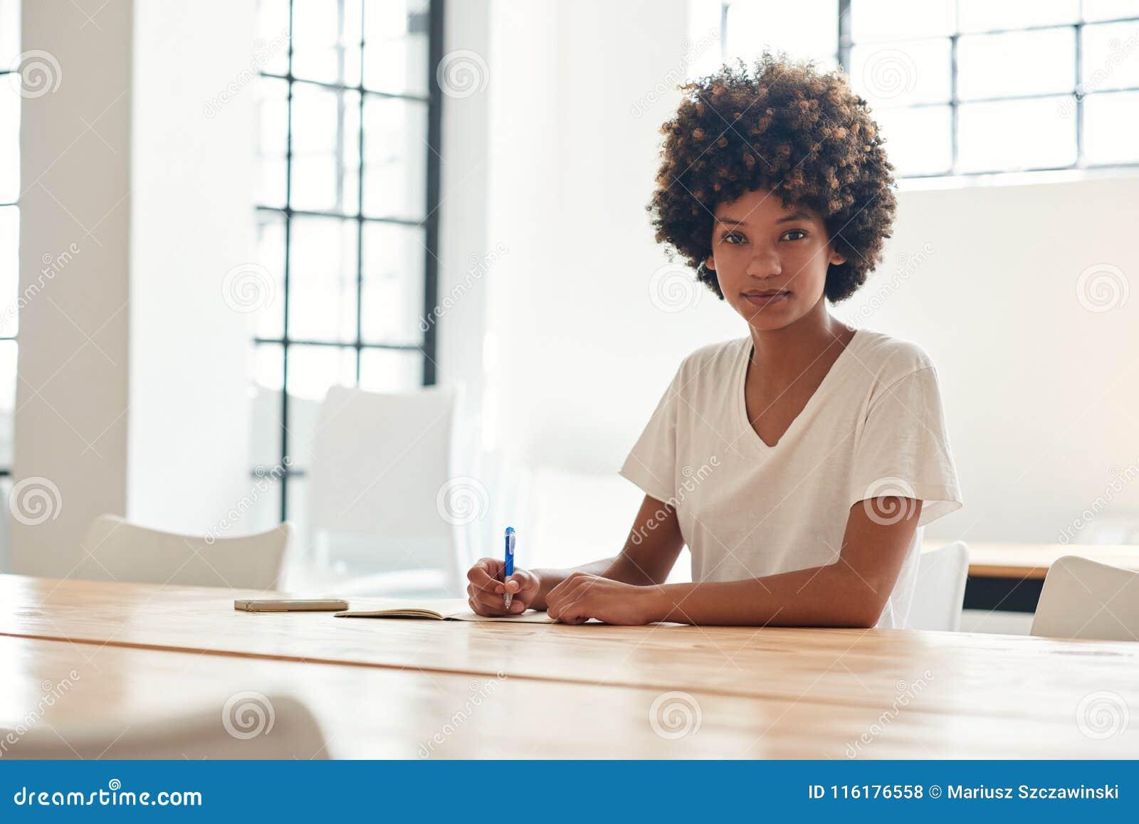 Jeune étudiante africaine sûre étudiant à une table de campus