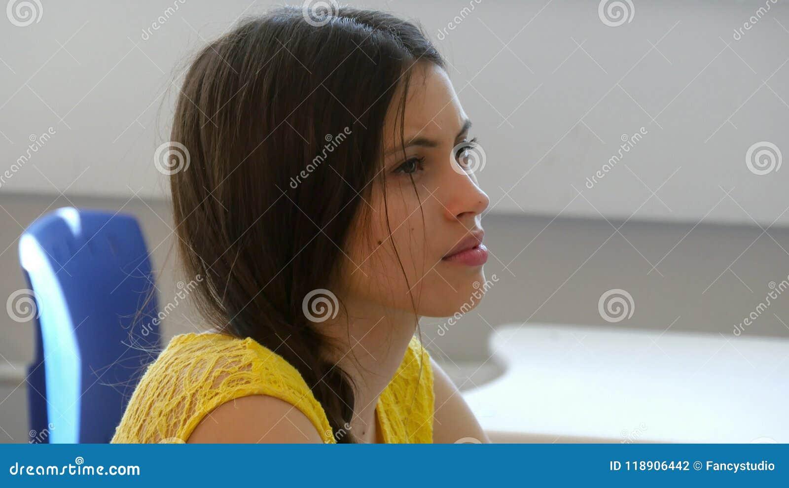 Jeune étudiante dans la salle de classe écoutant un conférencier