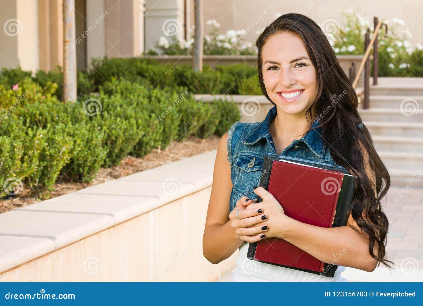 Jeune étudiante de métis avec des livres d école sur le campus