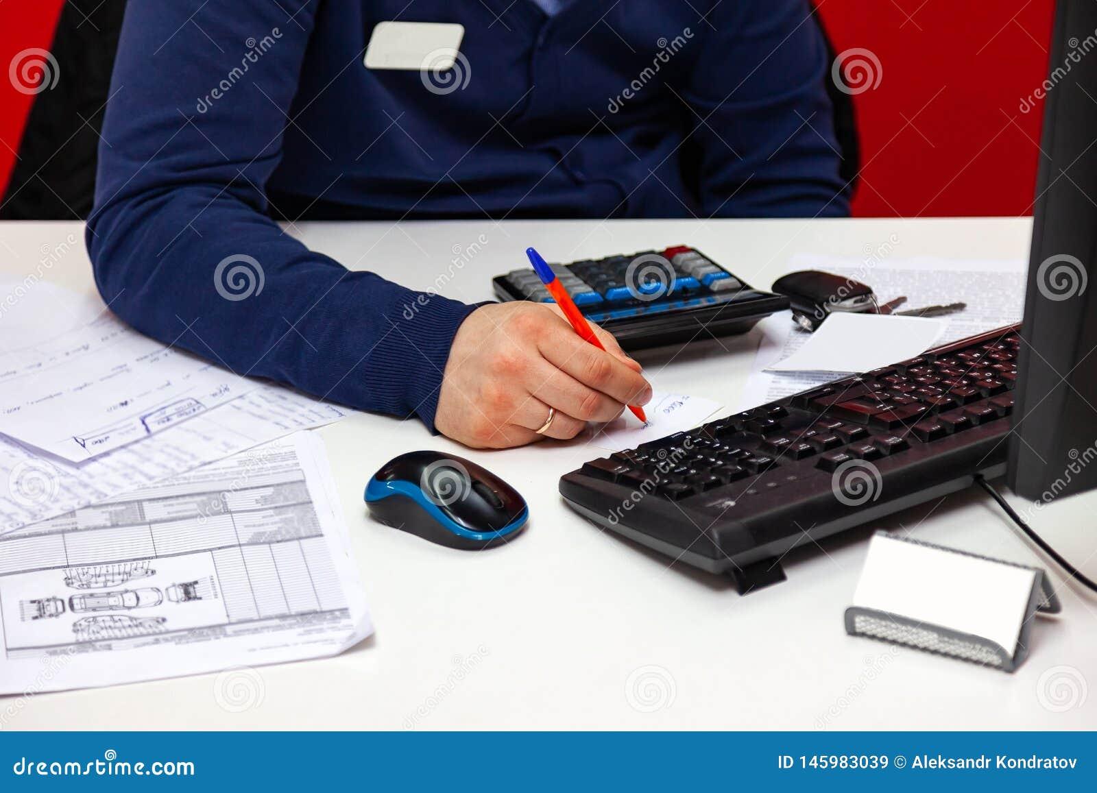 Jeune administrateur masculin parlant au t?l?phone au travail, tenant le t?l?phone ? son oreille et en m?me temps faisant des not