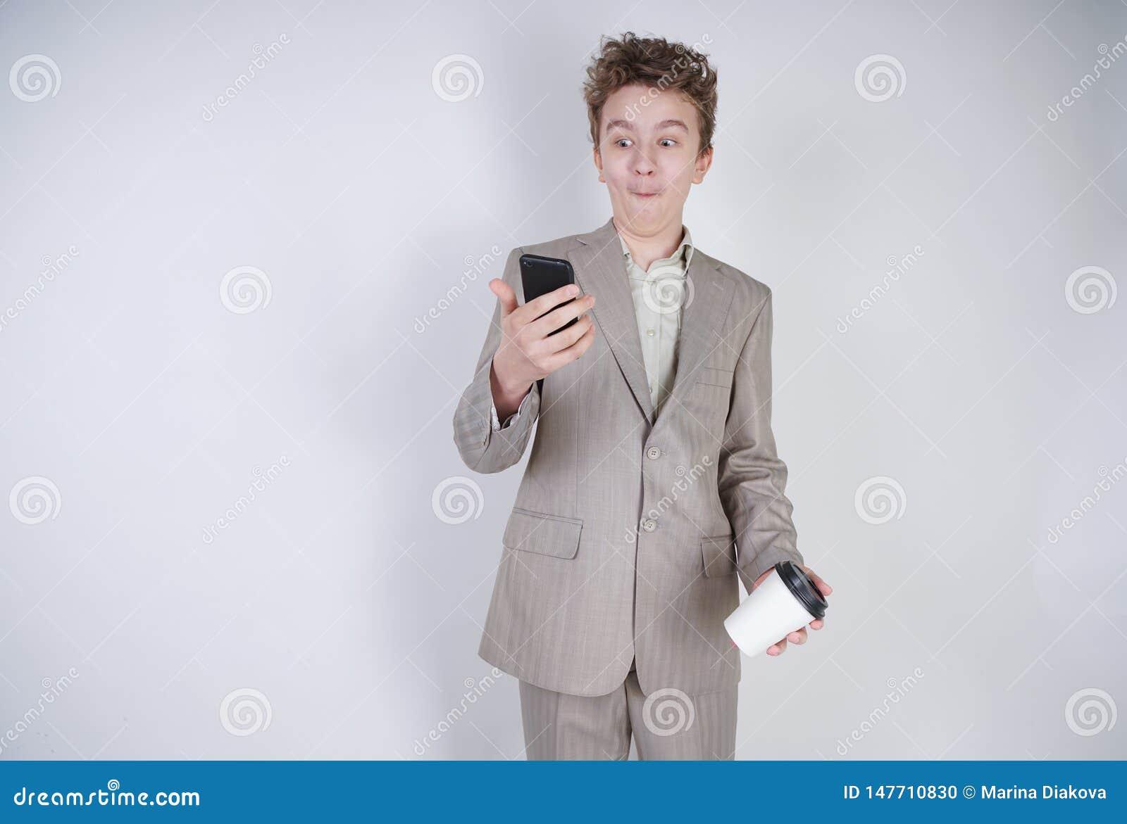 Jeune adolescent avec des émotions étonnées dans des vêtements gris d affaires se tenant avec la tasse de téléphone portable et d
