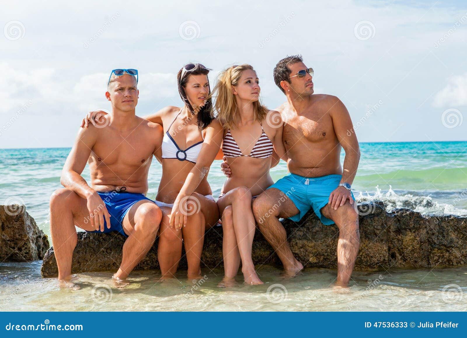 Jeune amusement heureux de havin d amis sur la plage
