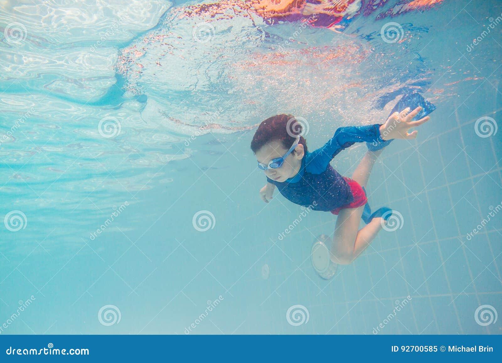Jeune amusement sous-marin de garçon dans la piscine avec des lunettes Amusement de vacances d été