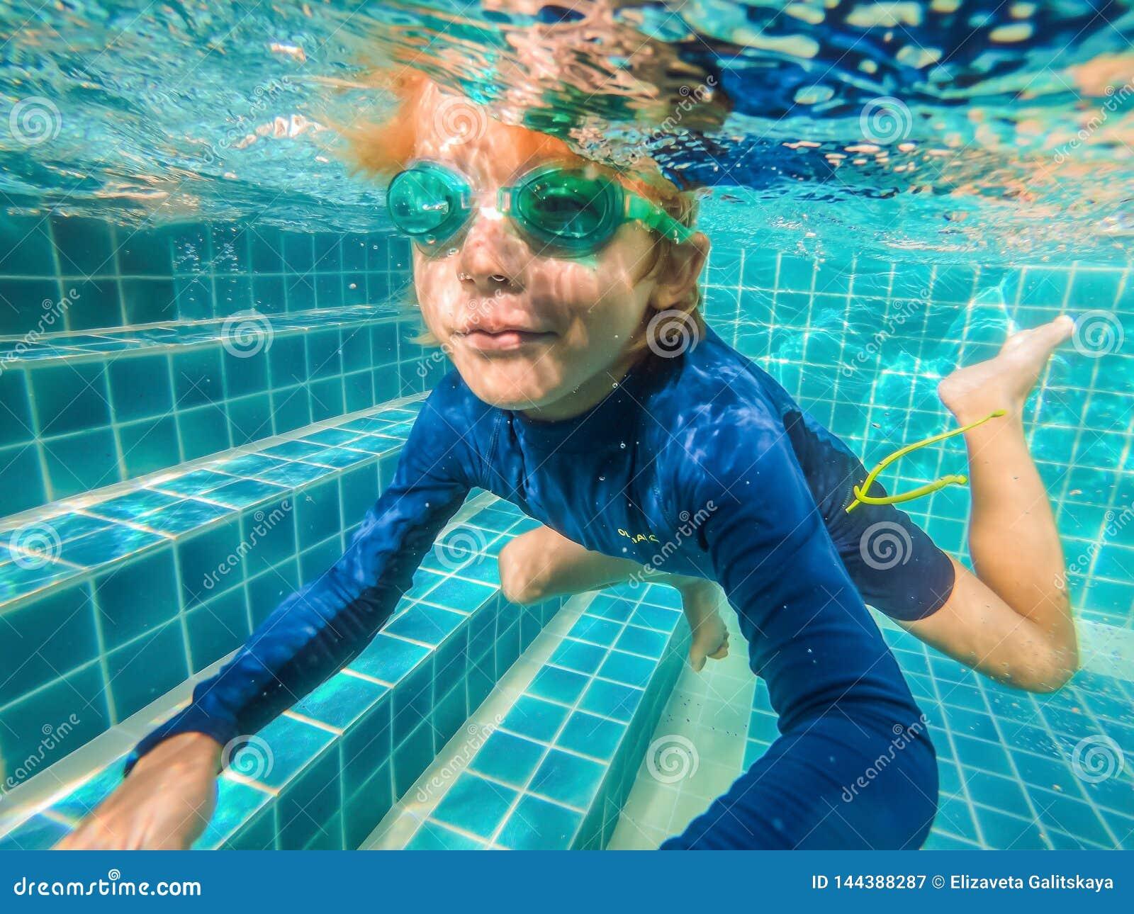 Jeune amusement sous-marin de gar?on dans la piscine avec des lunettes Amusement de vacances d ?t?