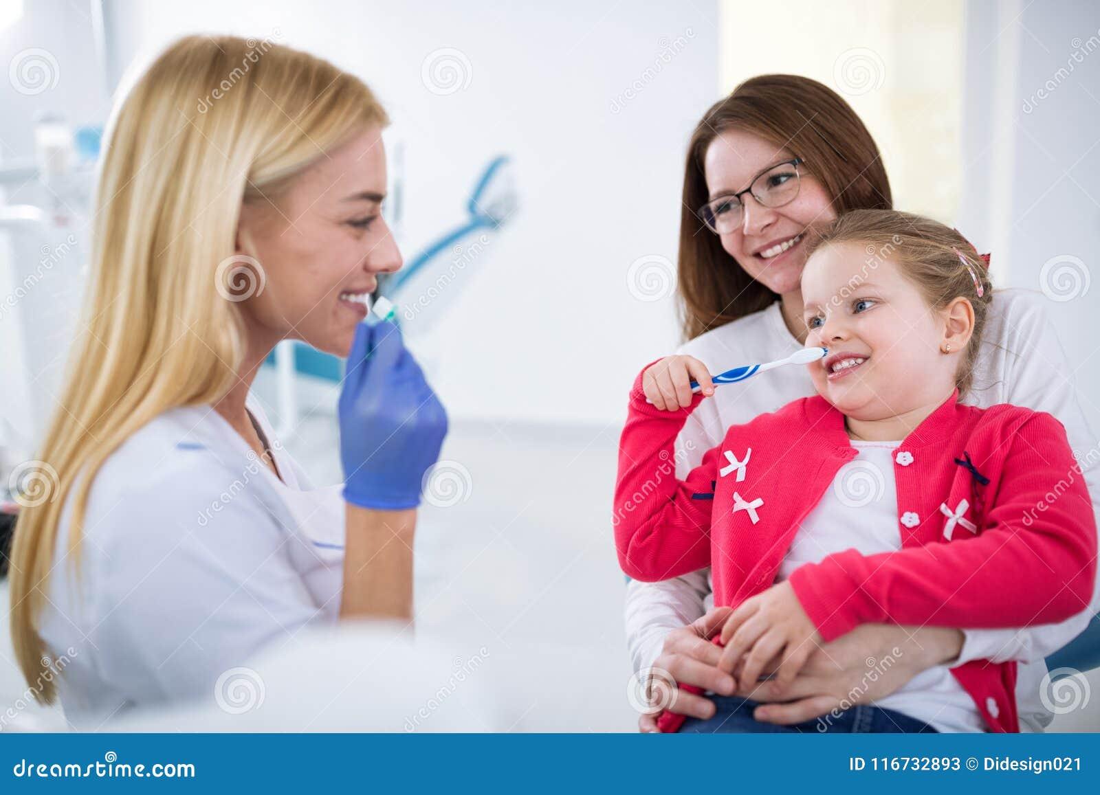 Jeune apparence femelle de dentiste comment laver des dents