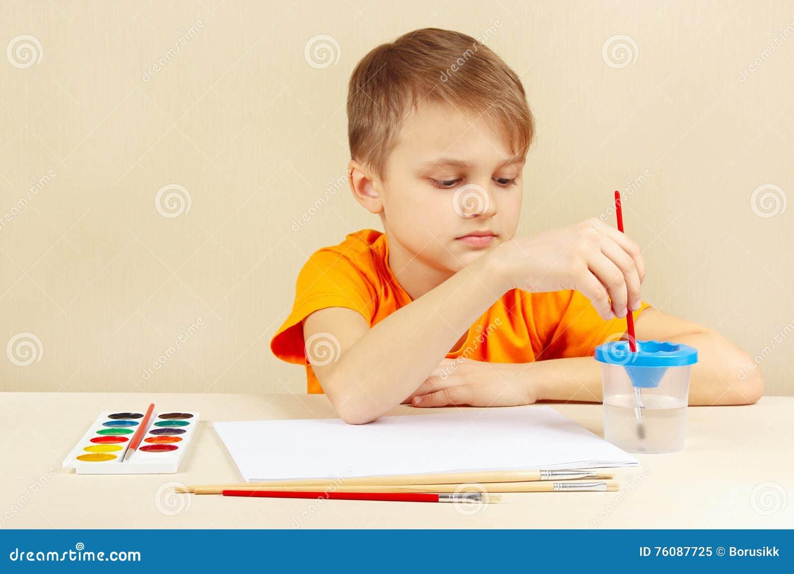 Jeune artiste dans la chemise orange allant peindre des couleurs
