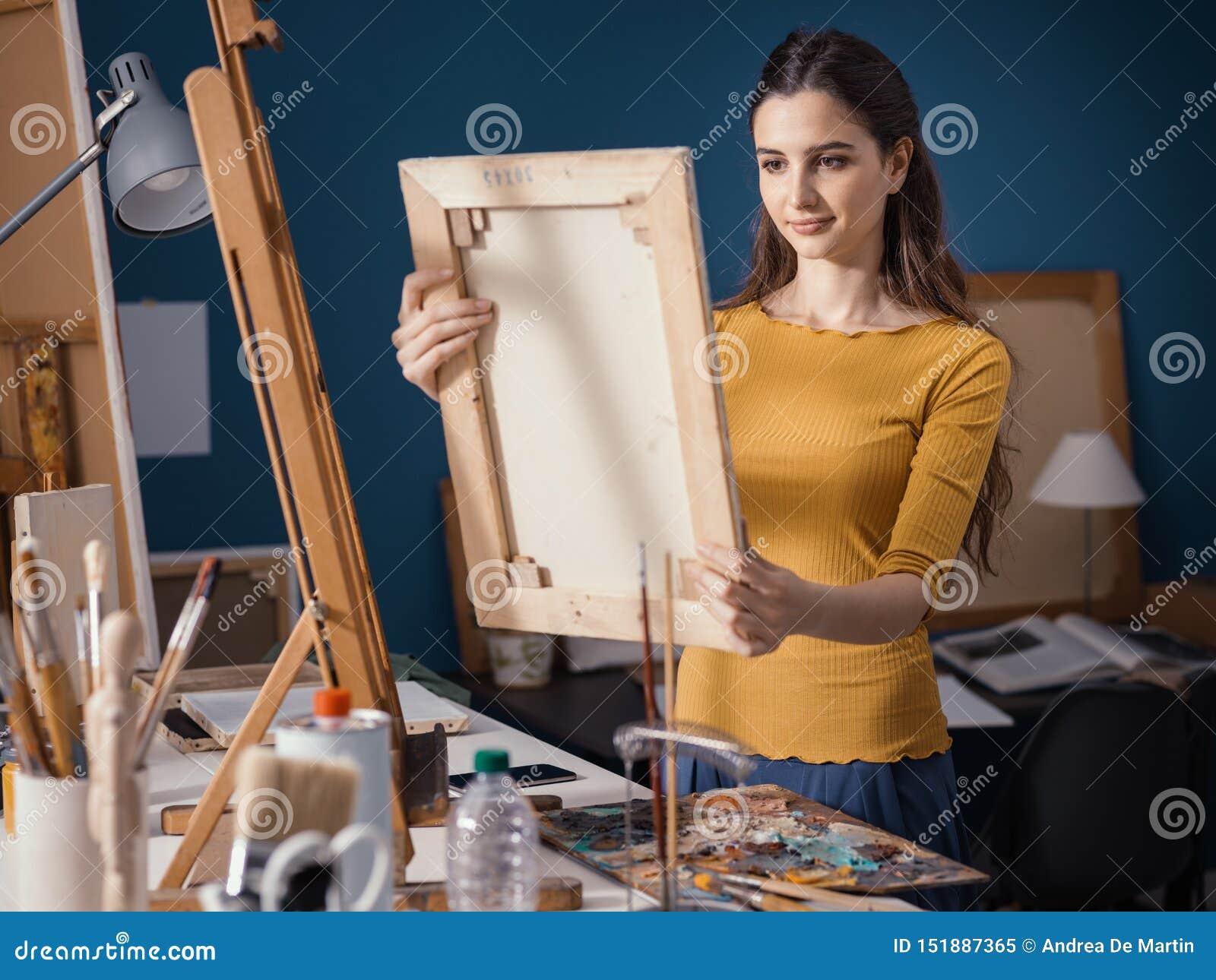 Jeune artiste mettant une toile sur le chevalet