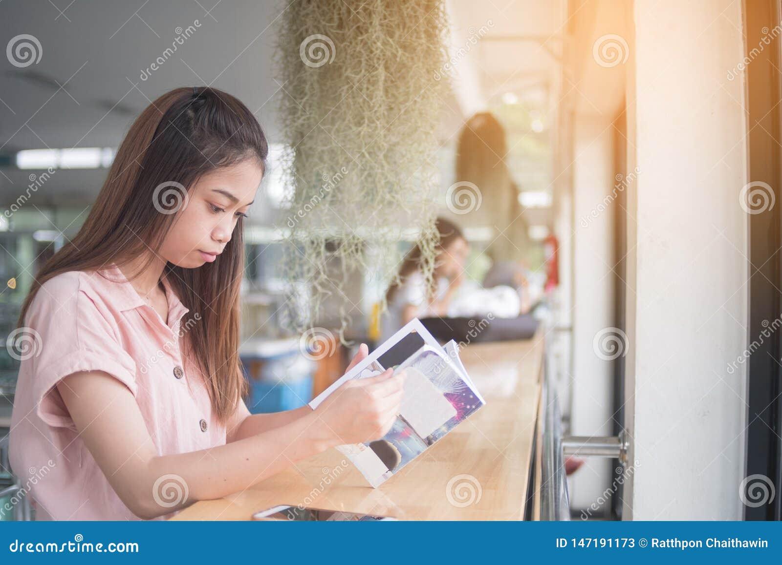 Jeune Asiatique lisant le livre se reposant à la barre de bureau